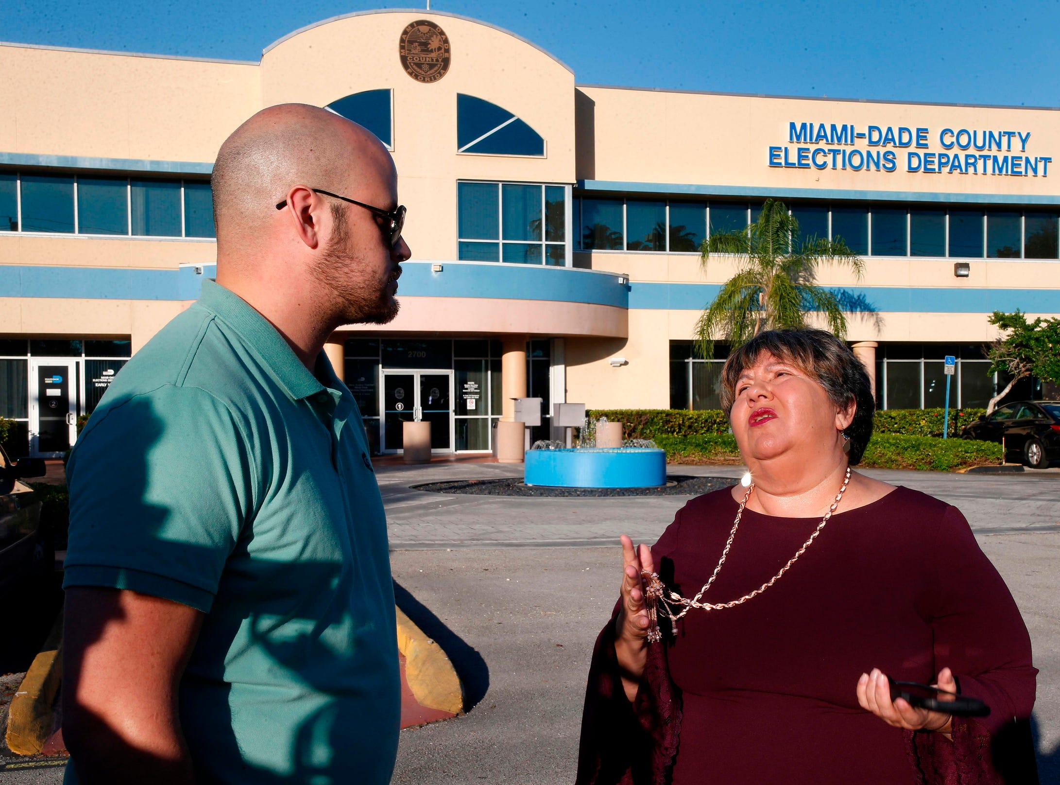 Convicted felons Daniel Torna (L) and Yraida Guanipa (R) share stories before heading in to the Miami-Dade County Elections Department to register to vote in Miami, Tuesday.  Some 1.4 million people in Florida can begin registering to vote on Tuesday after the state's electorate ended a measure banning suffrage for people with felony convictions.