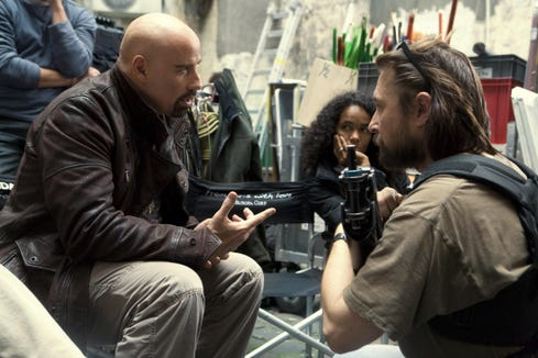 """Director Pierre Morel, right, with John Travolta on the set of the 2010 movie """"From Paris With Love."""" Travolta shaved his head for the role."""