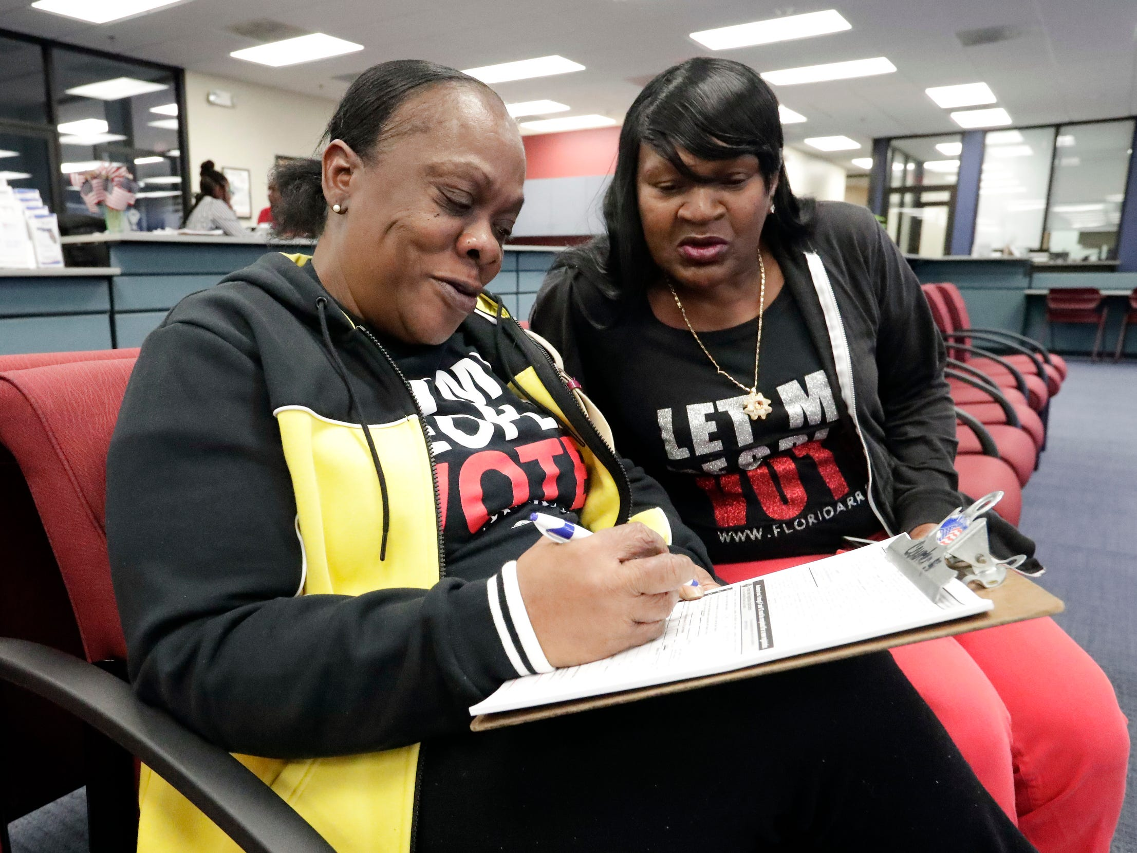 Former felon Yolanda Wilcox, left, fills out a voter registration form as her best friend Gale Buswell looks on at the Supervisor of Elections office in Orlando, Fla.