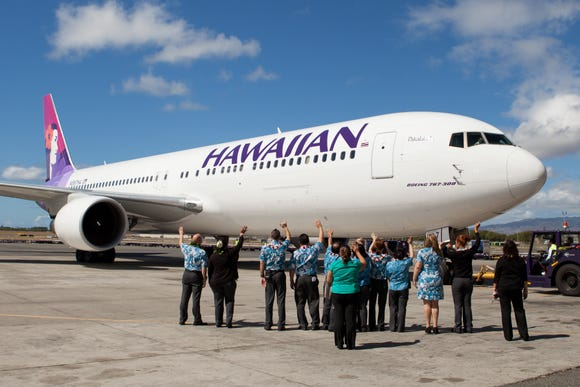 This file photo from 2012 shows Hawaiian Airlines crew waiving farewell to a Boeing 767 as the carrier launched non-stop service between Hawaii and Sapporo, Japan.