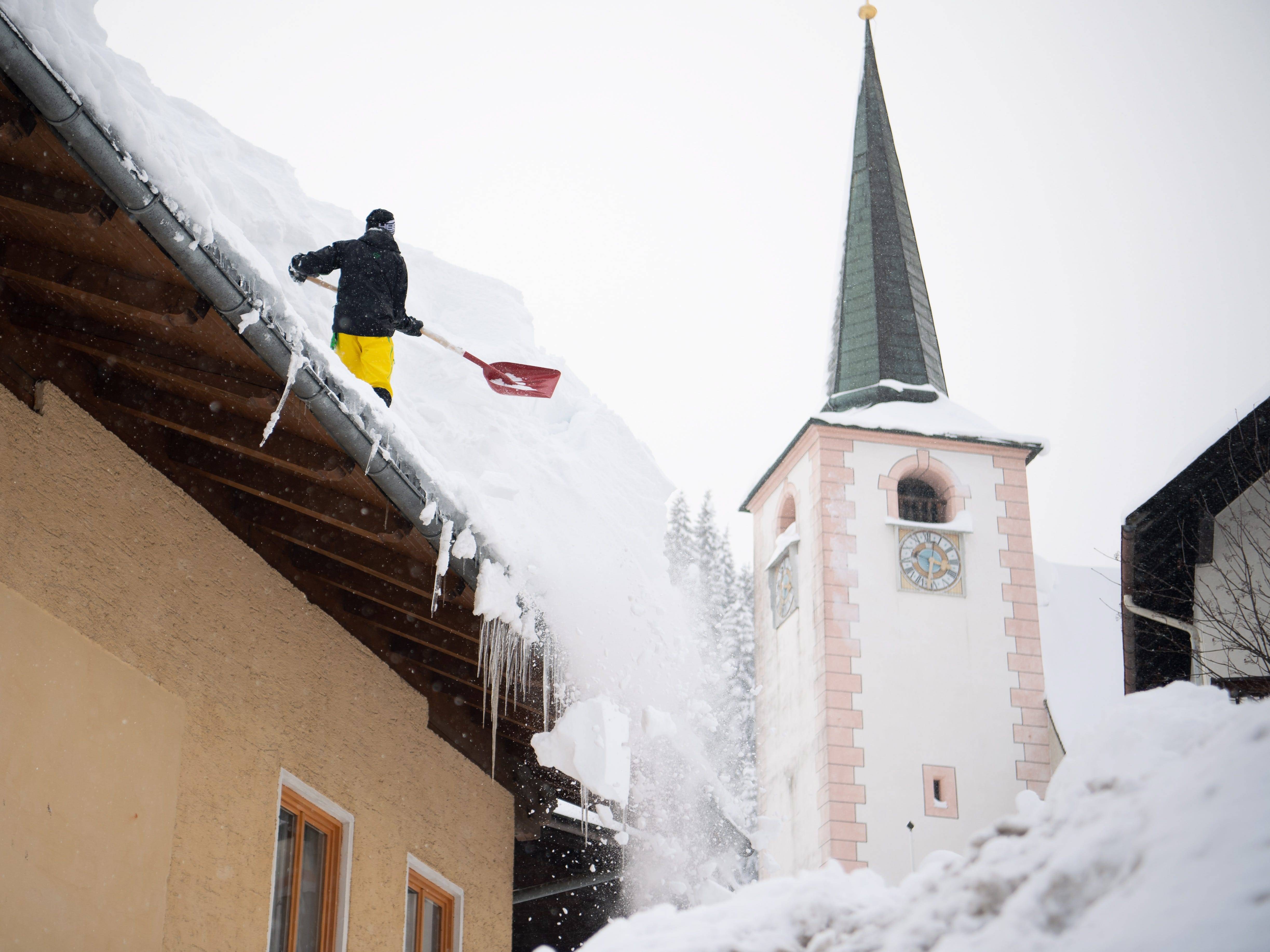 A msn tries to remove snow from a roof of a house in Filzmoos, Austria, Jan. 8, 2019.