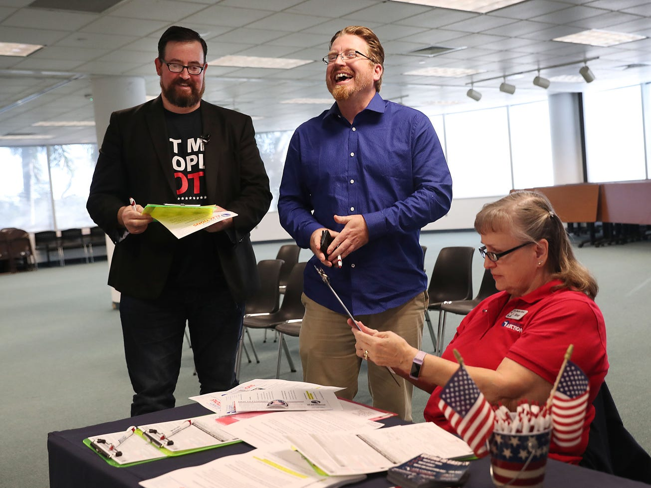 Neil Volz (L) and Lance Wissinger (C) fill out their voter registration forms with the help of Rosey Brockamp, a voter registration worker at the Lee Country Supervisor of Elections office.