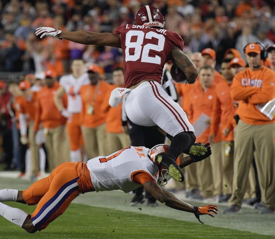Alabama tight end Irv Smith Jr. tries to avoid the tackle of Clemson cornerback Trayvon Mullen during the 2019 College Football Playoff championship game.