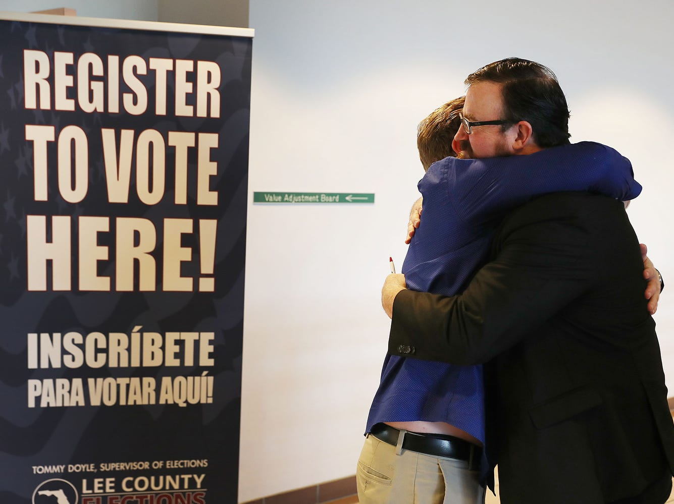 Lance Wissinger, left, and Neil Volz hug after turning in their voter registration forms at the Lee County Supervisor of Elections office in Fort Myers, Fla. Both with felony records, are now able to register to vote for the first time after Amendment 4 took effect, which  automatically restores voting rights to most felons.
