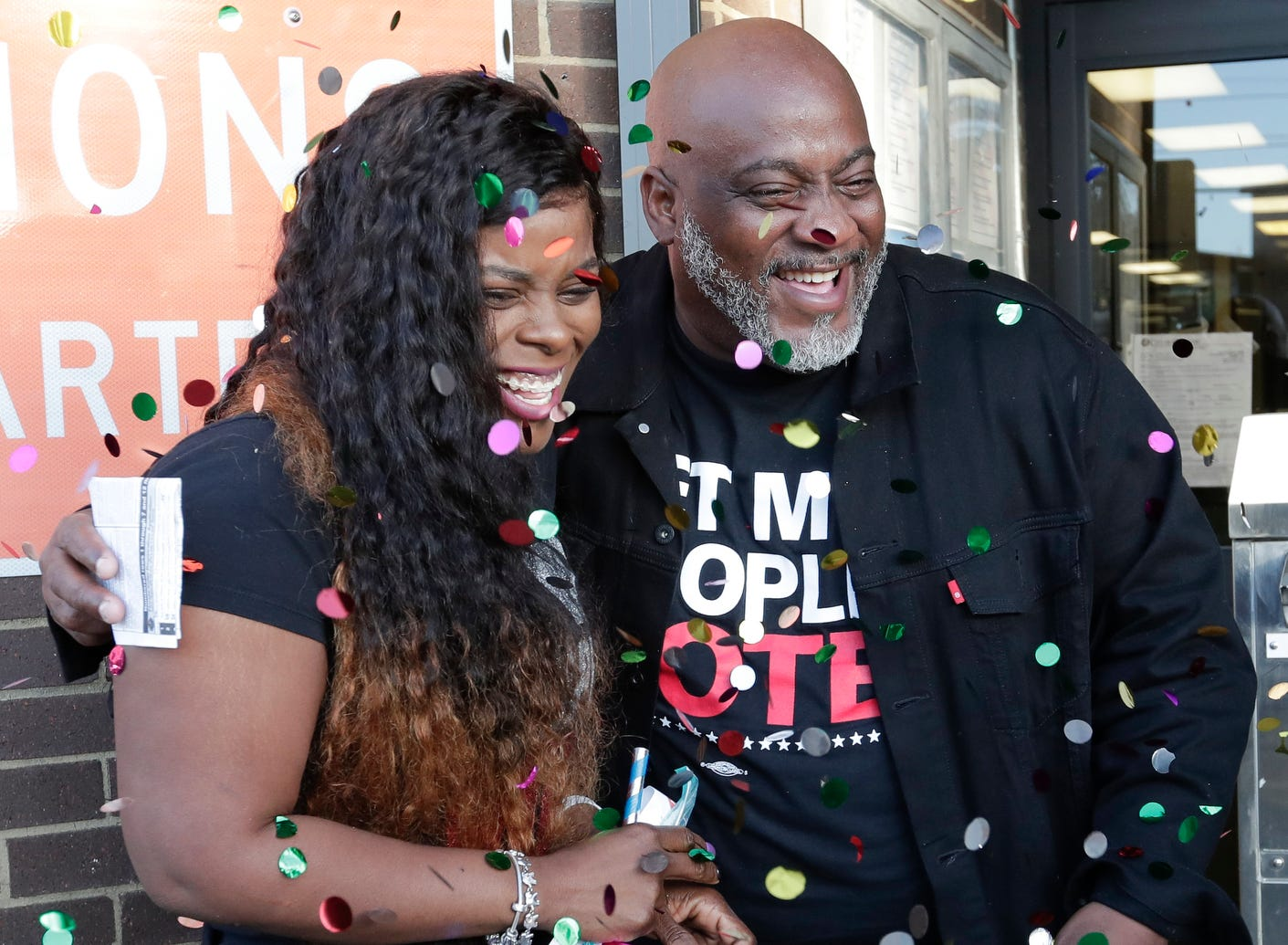 Former felon Desmond Meade and president of the Florida Rights Restoration Coalition, right, celebrates with his wife Sheena as family members covered them with confetti after he registered to vote at the Supervisor of Elections office on Jan. 8, 2019, in Orlando, Fla.