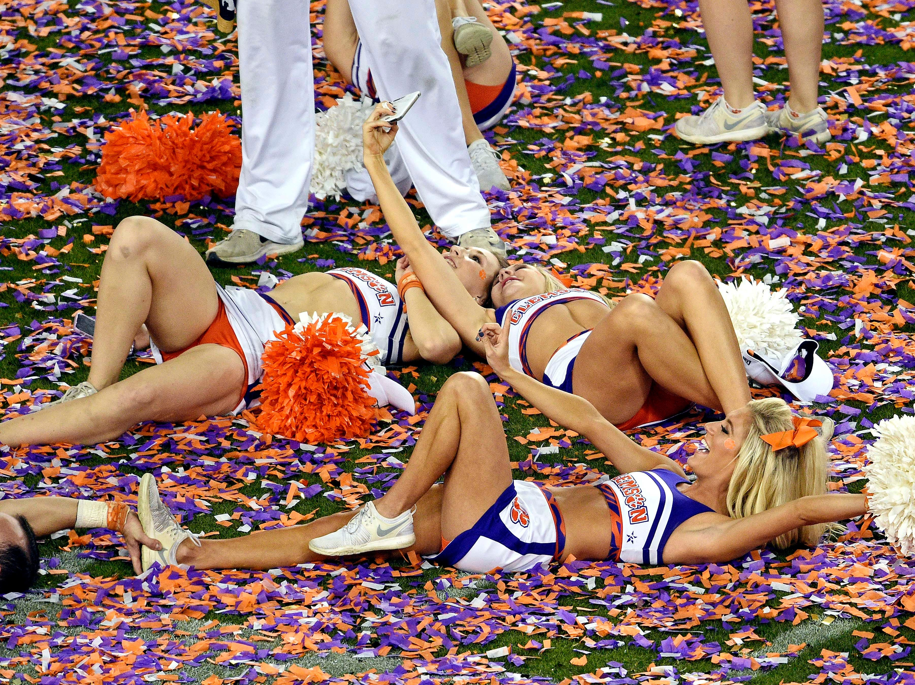 Clemson cheerleaders celebrate on the field after the game.