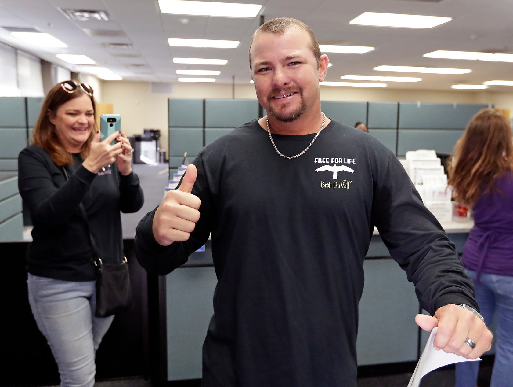 Former felon Brett DuVall gives a thumbs up as his wife Dottie takes a photo after he registered to vote at the Supervisor of Elections office Tuesday, in Orlando, Fla.