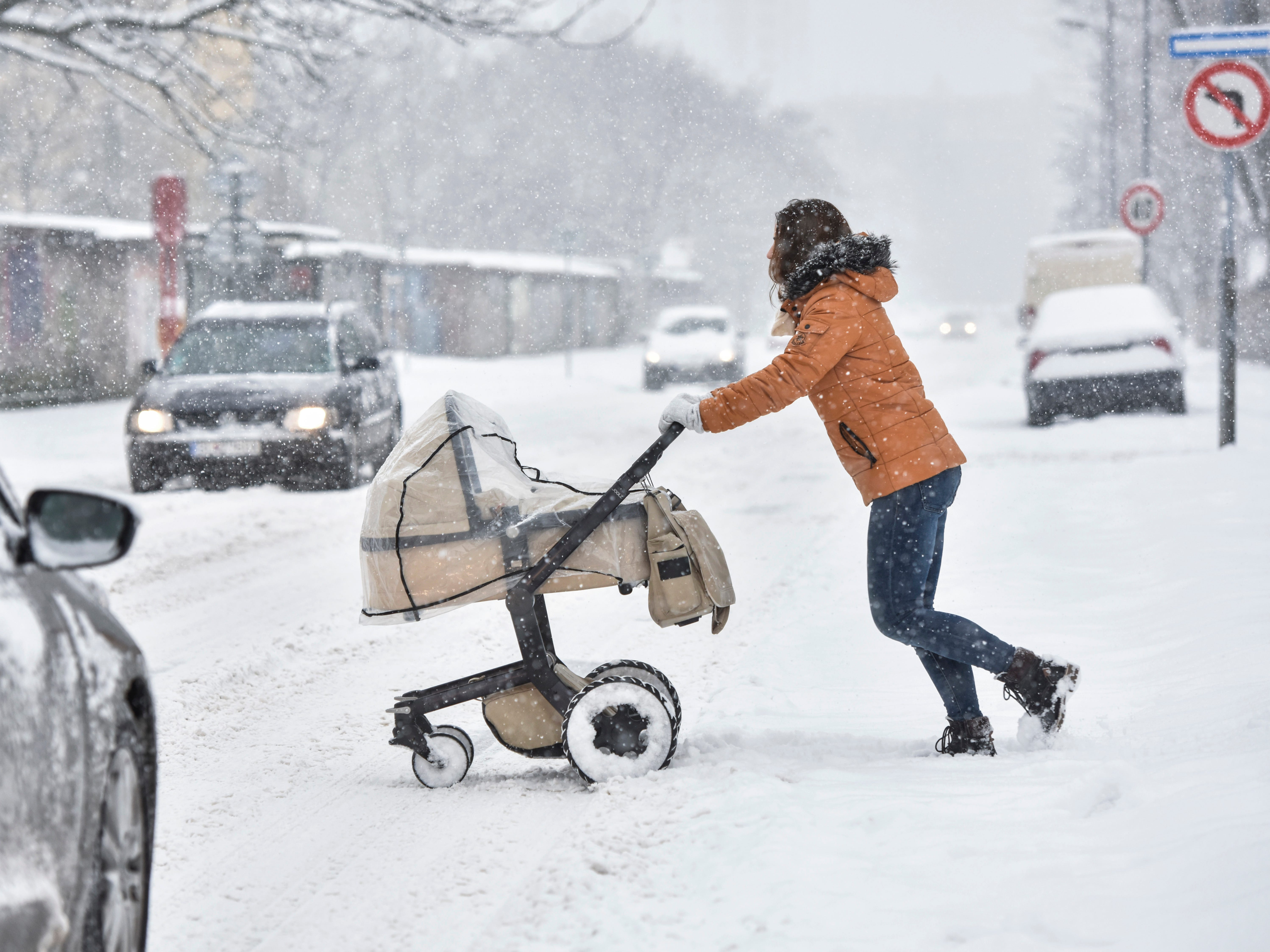 A woman pushes a pram across the street during heavy snowfall in Bratislava, Slovakia, Jan. 8, 2019. Cold weather has engulfed many parts of Europe.