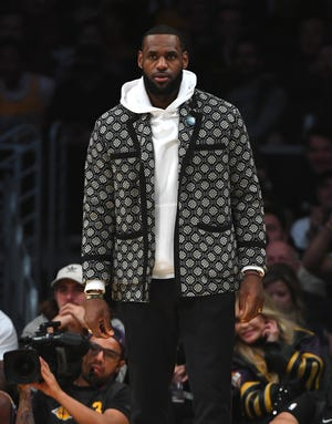 Los Angeles Lakers forward LeBron James looks on from the bench.