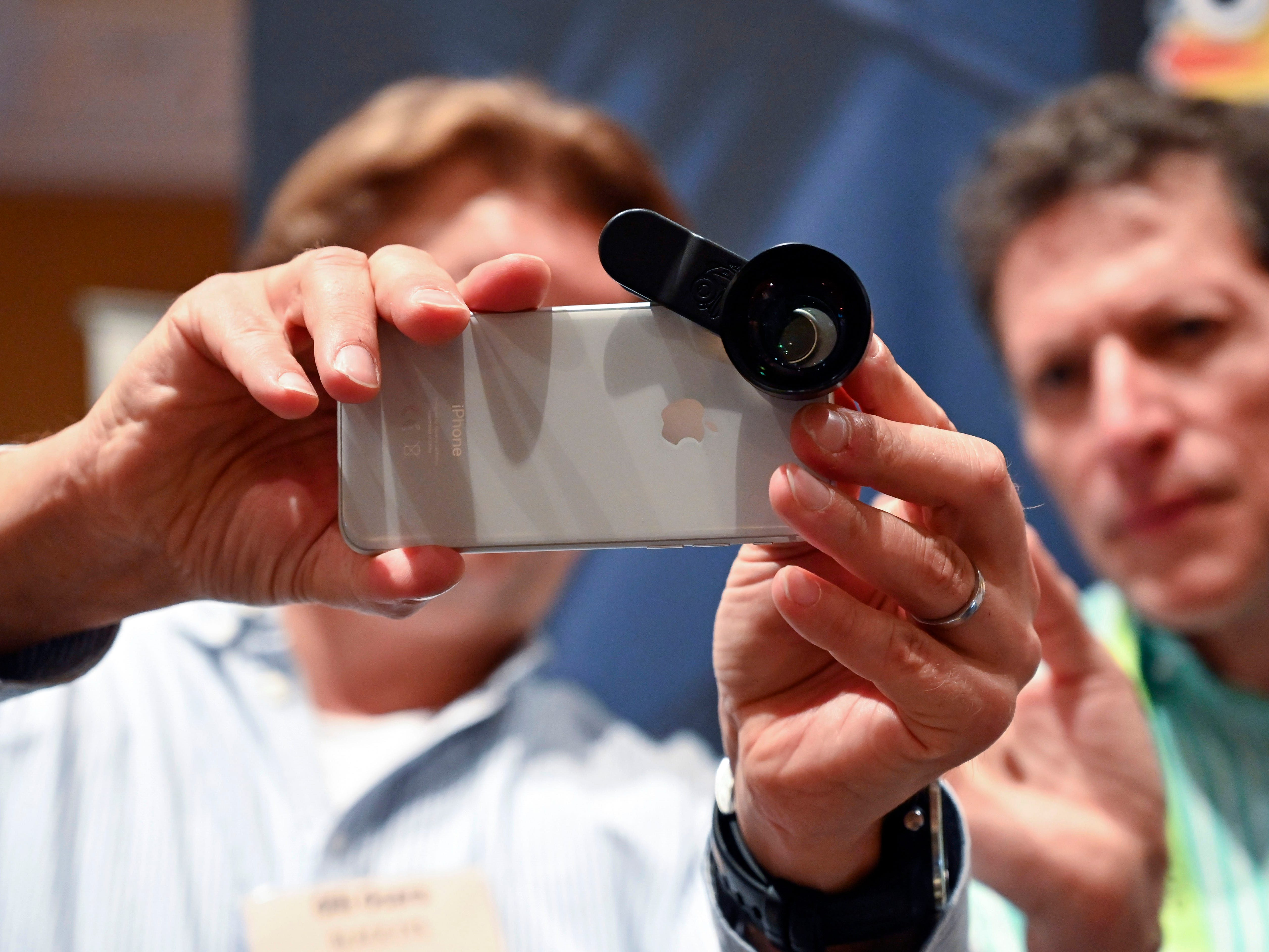 Olli Osara demonstrates a clip on lens for cellphone to Arnie Weissmann at the Black Eye booth.