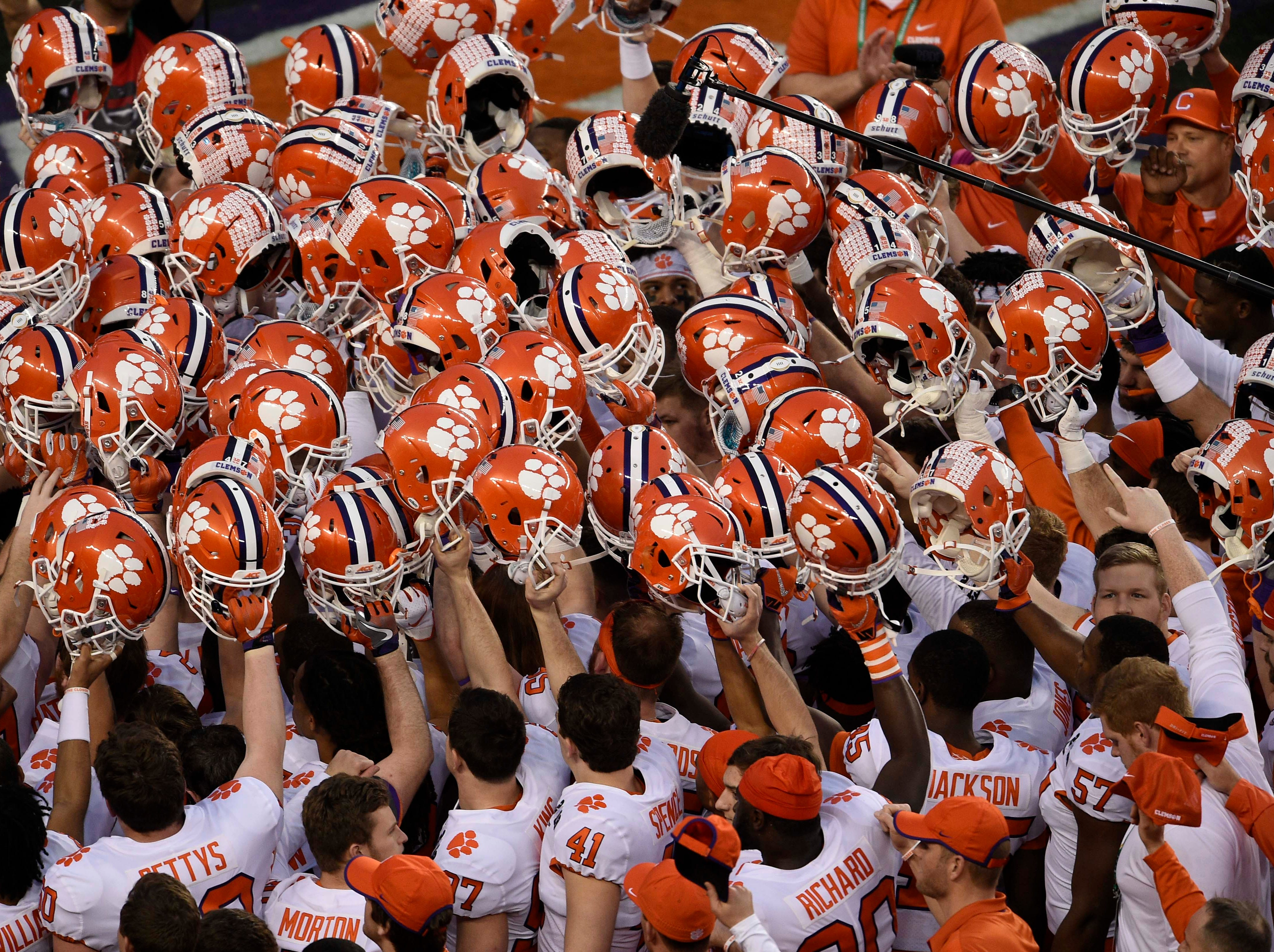 Clemson players raise their helmets before the game.