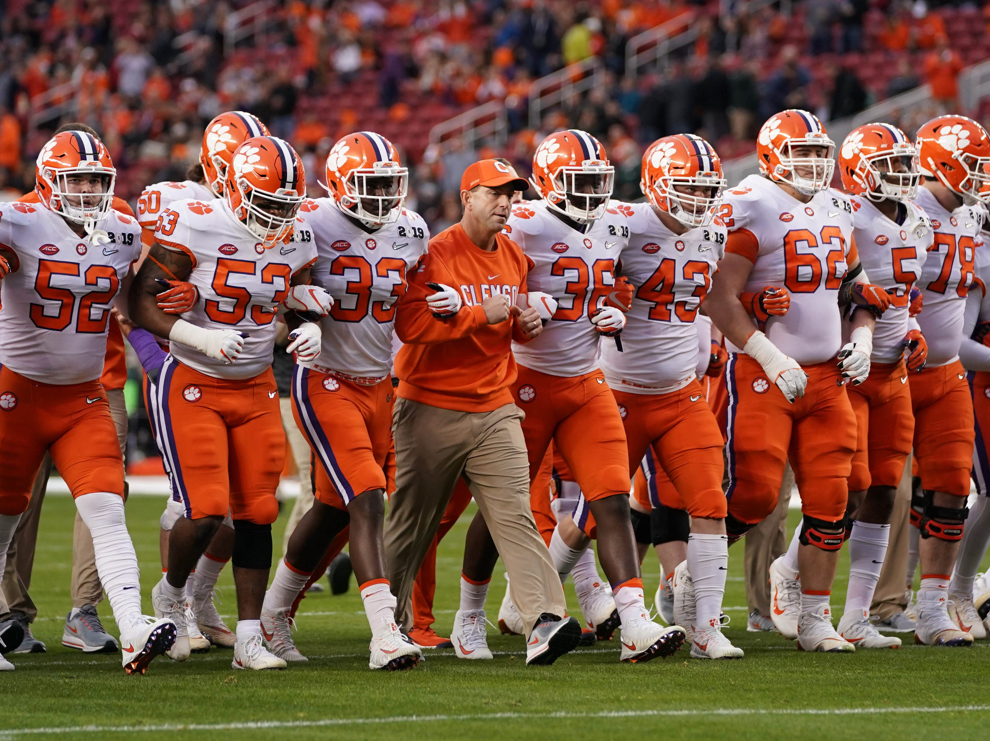 Dabo Swinney locks arms with his team before the game.