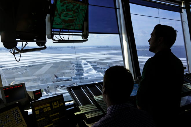 In this March 16, 2017, file photo, air traffic controllers work in the tower at John F. Kennedy International Airport in New York.
