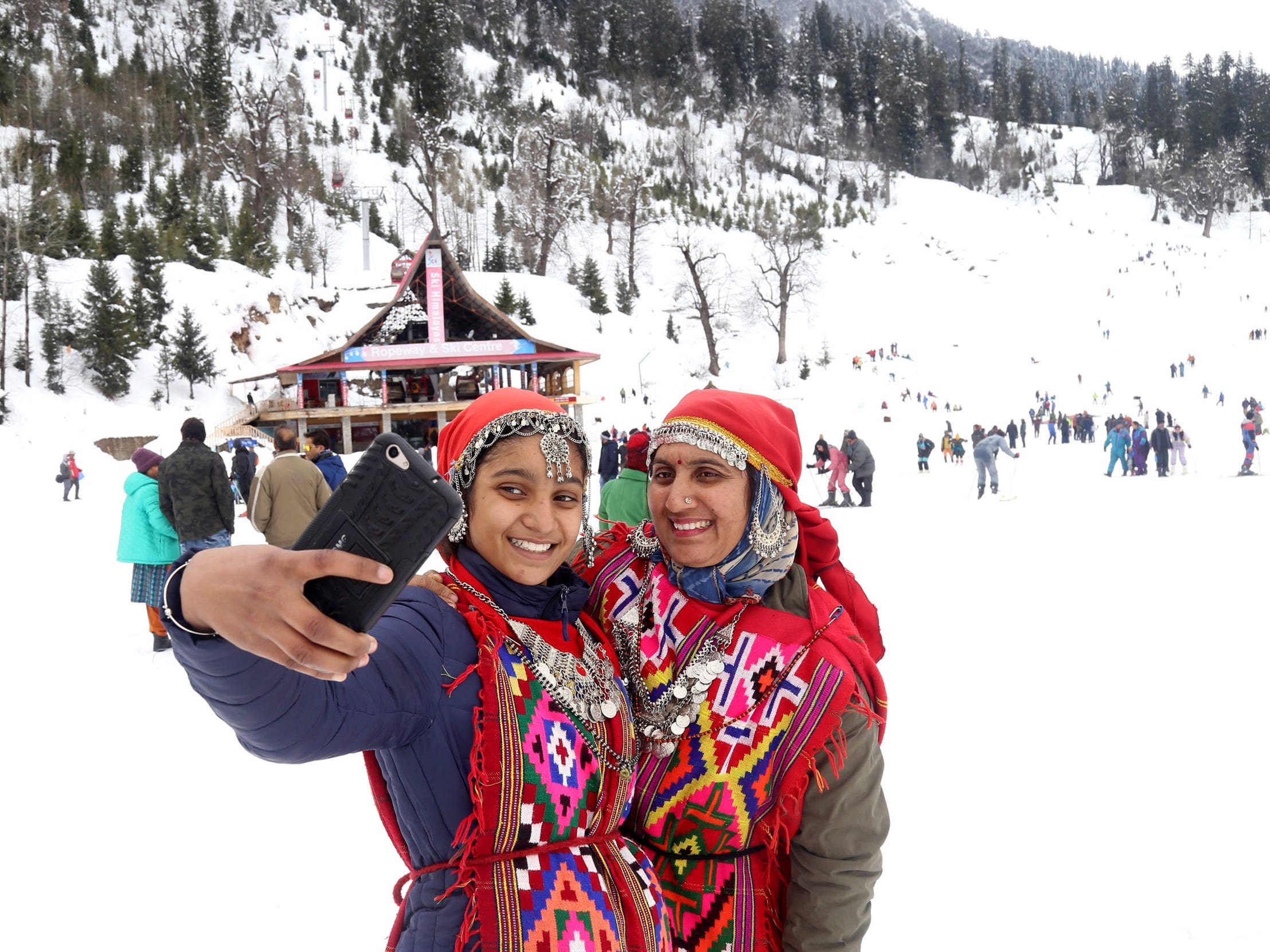 Women wearing traditional Himachali attire take selfies in the snow covered Solang Nala area near Manali, India, Jan. 8, 2019.