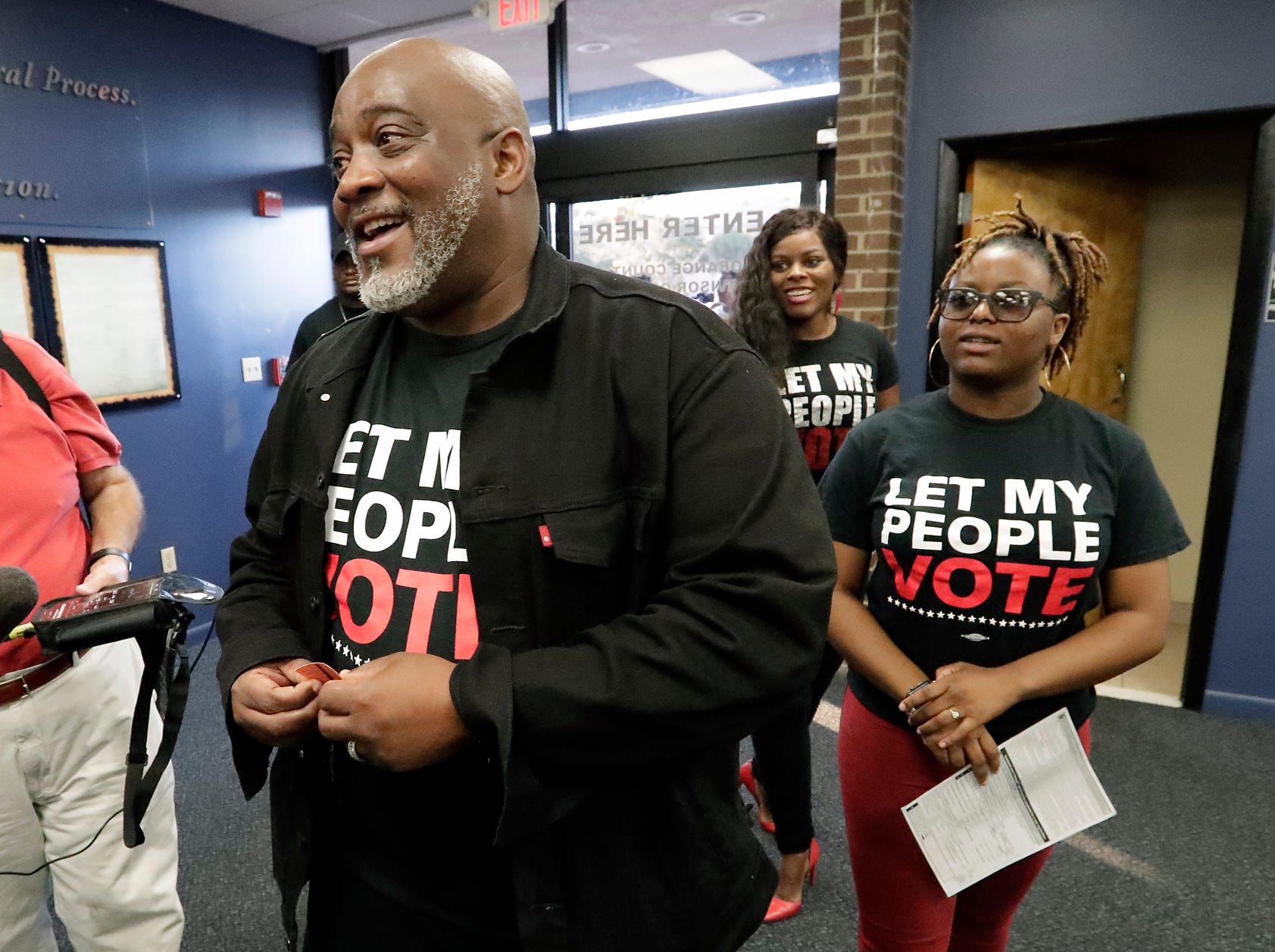 Former felon Desmond Meade and president of the Florida Rights Restoration Coalition, left, arrives with family members at the Supervisor of Elections office  in Orlando, Fla., to register to vote, Tuesday.