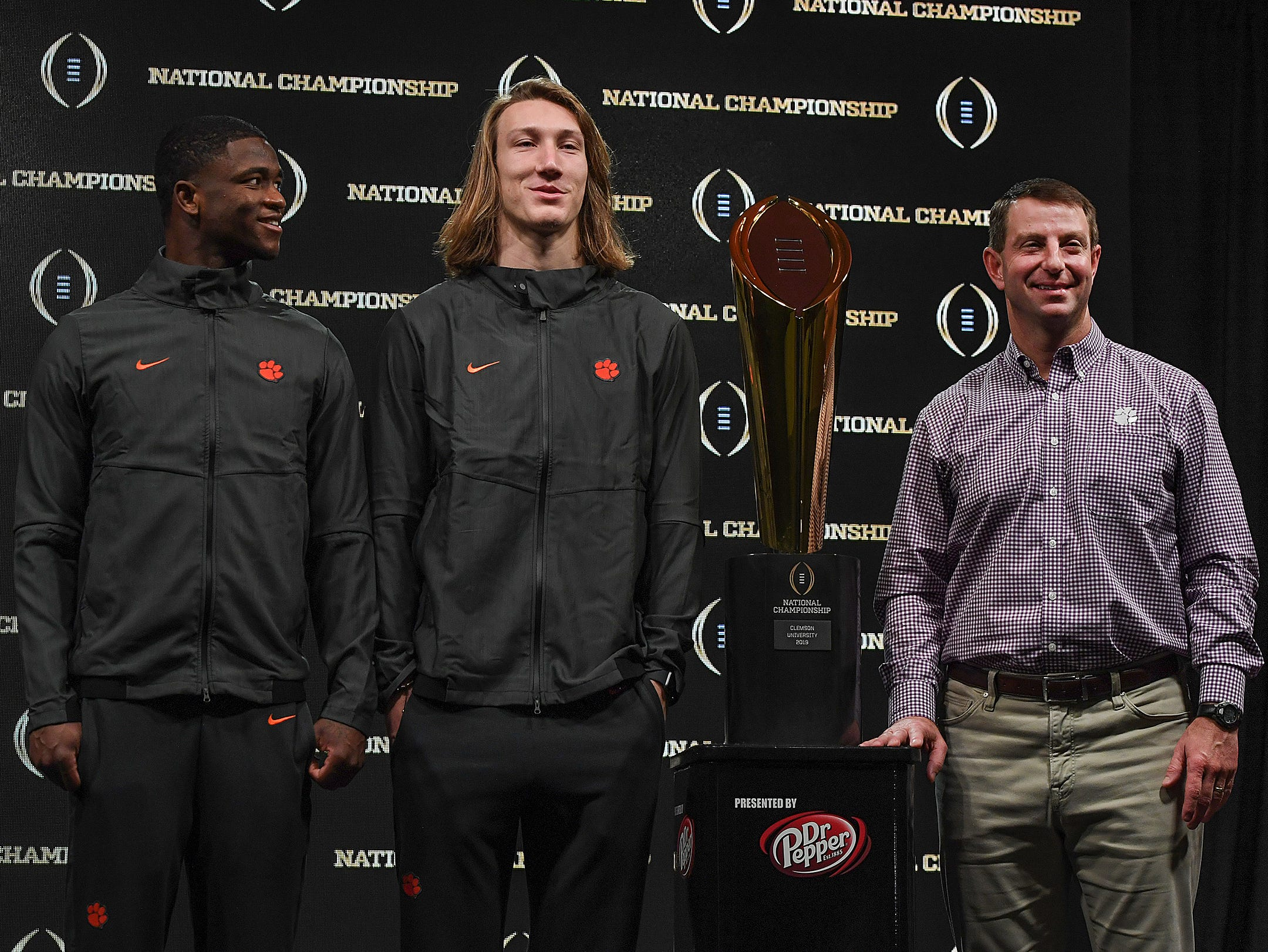 From left, defensive MVP Clemson cornerback Trayvon Mullen, offensive MVP quarterback Trevor Lawrence and head coach Dabo Swinney stand with their College Football National Championship trophy during a press conference in San Jose, CA Tuesday, January 8, 2019.