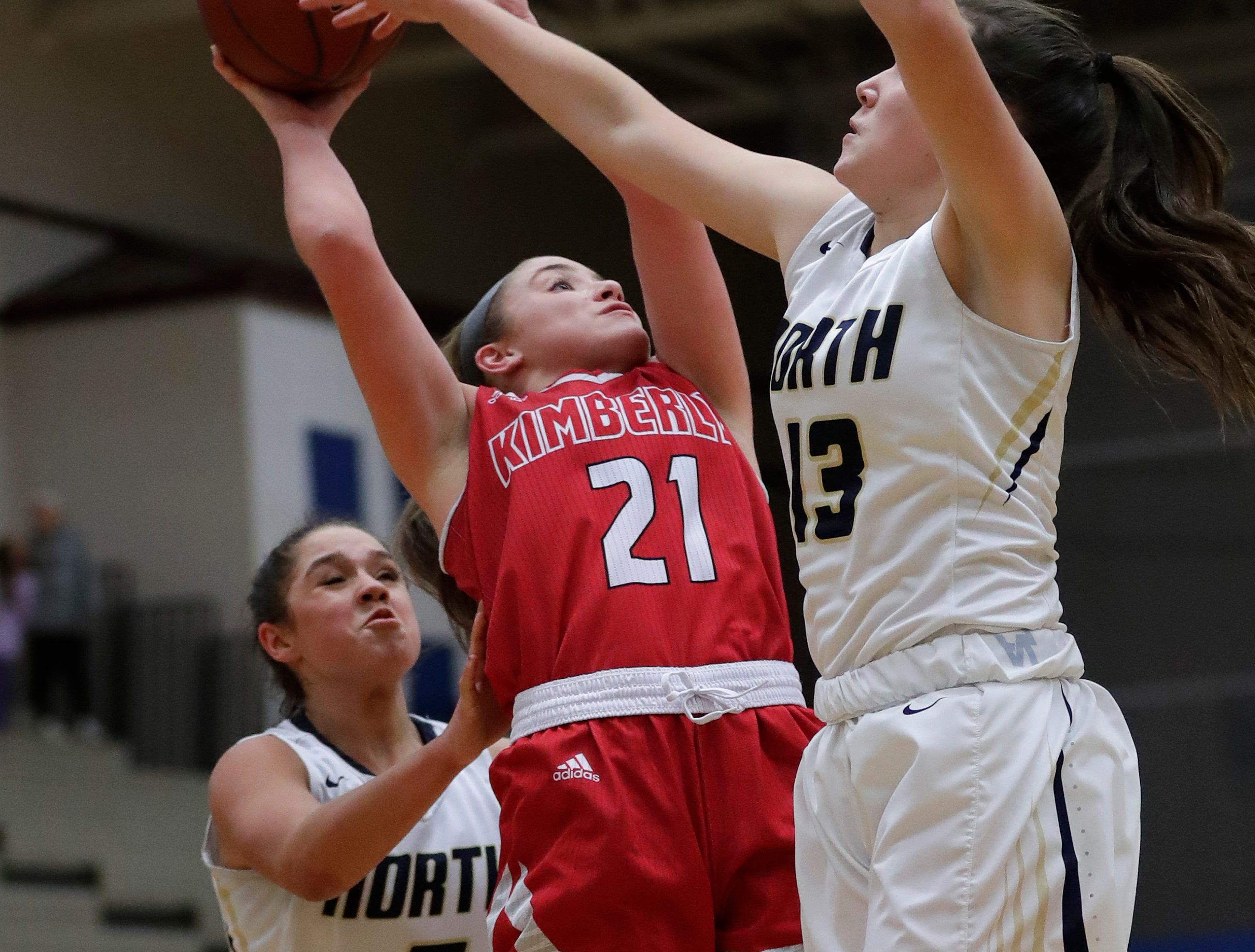 Kimberly High School's Kate Karch (21) puts up a shot against Appleton North High School's Niki Van Wyk (5) and Natalie Dvoracek (13) during their girls basketball game Tuesday, January 8, 2019, in Appleton, Wis. Dan Powers/USA TODAY NETWORK-Wisconsin