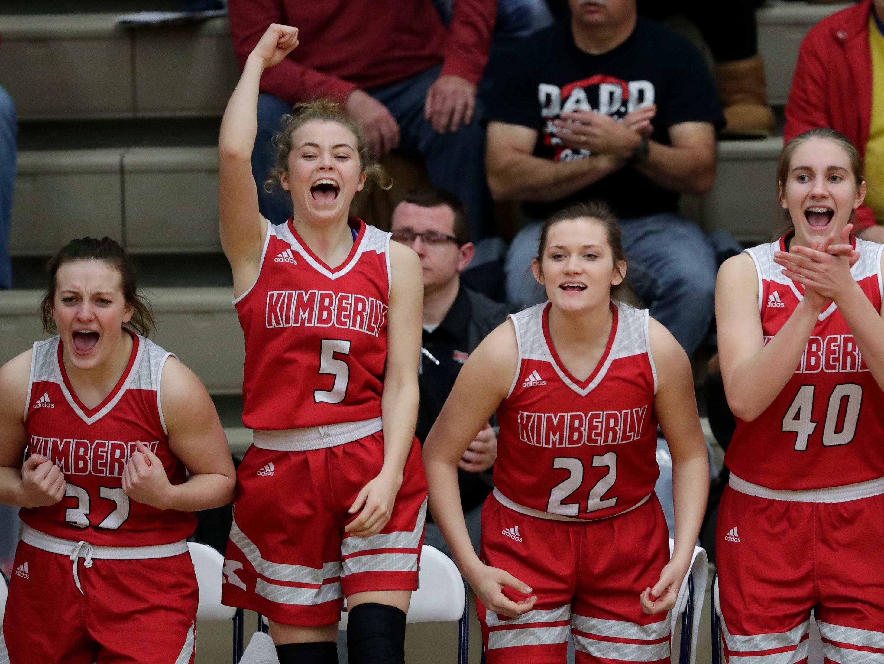 Kimberly High School's Emma Kilatrick (32), Paige Cullen (5), Kennedy Litvinoff (22) and Kayla Behnke (40) cheer for their teammates after a basket scored against Appleton North High School during their girls basketball game Tuesday, January 8, 2019, in Appleton, Wis. 