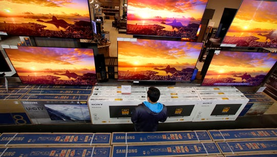 A man looks at televisions during an early 2018 Black Friday sale at a Best Buy store in Overland Park, Kan. If you have a few extra bucks that you don't need for necessities like rent or loan payments, consider shopping for happiness.