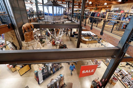 A carved mountain goat looks down at the lower level in REI Co-op's flagship store in Seattle.