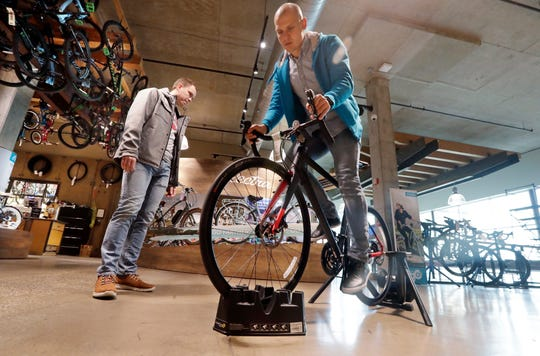 """Myroshnychenko, right, test rides a bike atop a stand as Denis Rybalchenko looks on in REI Co-op's flagship store in Seattle  in November 2018. The usual advice is """"buy experiences, not things."""" But that requires a deeper dive. A bicycle can provide an experience, and a new camera can preserve one. So buy experiences, especially with other people, but also think about buying material things that allow you to have experiences or enhance them."""