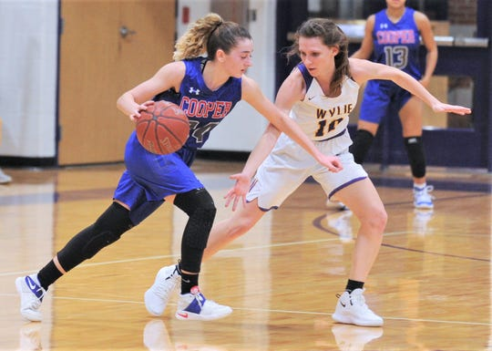 Wylie's Abbey Henson (10) defends against Cooper's Meri Tetaj. Wylie won the District 4-5A game 76-37 on Tuesday, Jan. 8, 2019, at Bulldog Gym.