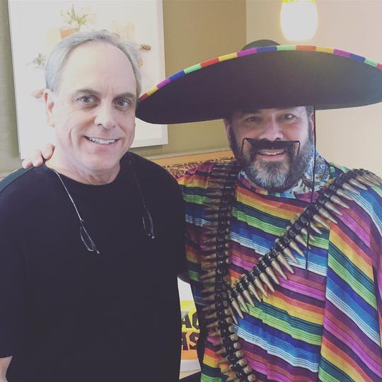 Kyle McAlister (right) poses as a character for Taco Casa.