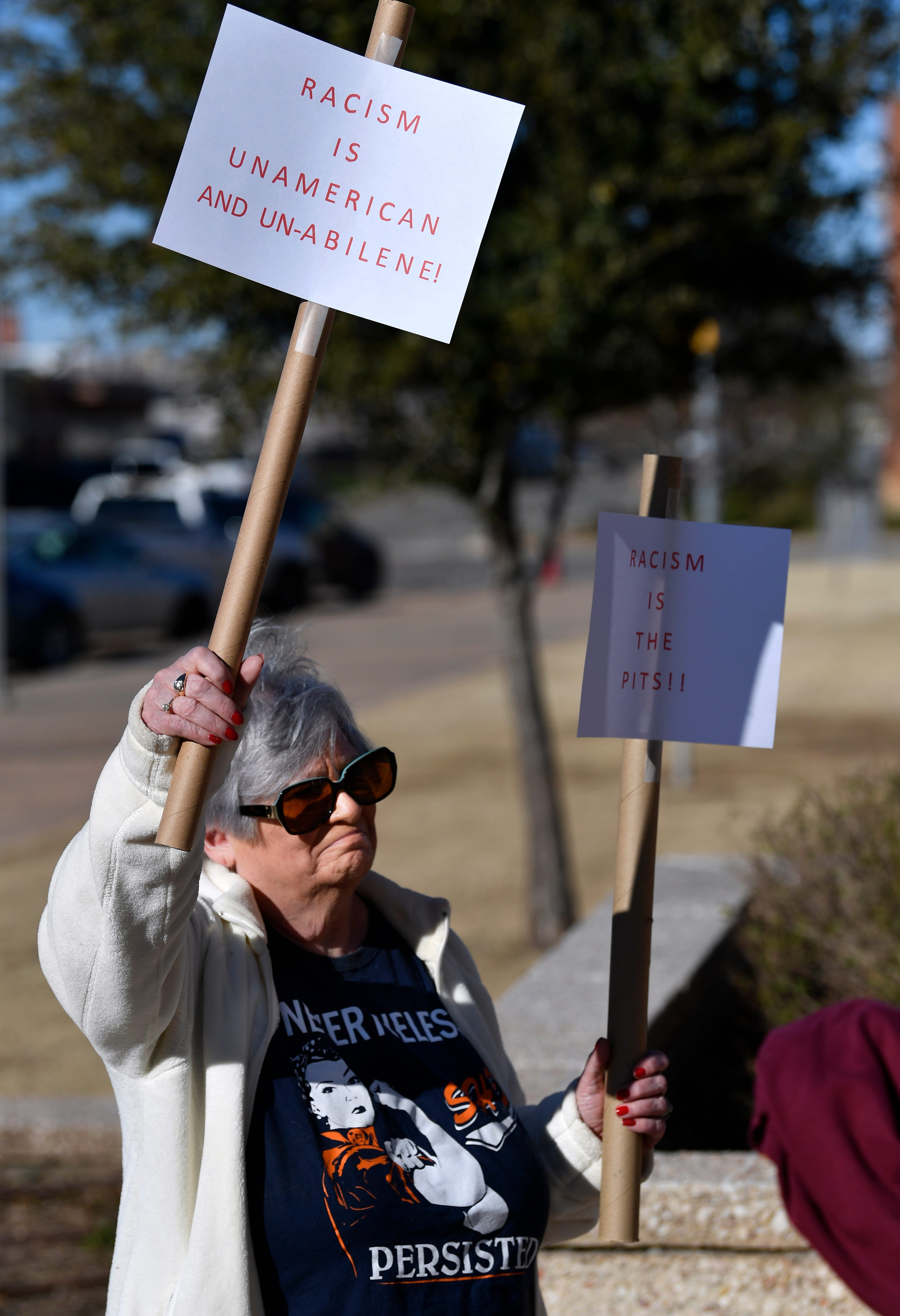 "Dianne Morphew holds a pair of signs decrying racism in front of Abilene City Hall on Wednesday. She was attending a press conference of Latino community leaders decrying social media postings by city councilman Kyle McAlister they labeled as racist. ""We are all immigrants; we need to work together and see each other as friends and equals,"" she said."