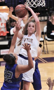 Wylie's Karis Christian shoots over Cooper's Jennika Willis (32). Wylie won the District 4-5A game 76-37 on Tuesday, Jan. 8, 2019, at Bulldog Gym.