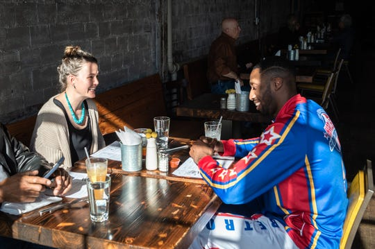 "Mackensy Lunsford, food writer at the Asheville Citizen Times, has lunch at Asheville's Buxton Hall BBQ with Chandler ""Bulldog"" Mack, a player on the Harlem Globetrotters exhibition basketball team and self-proclaimed foodie, Jan. 8, 2019. The team is playing at Asheville's U.S Cellular Center on Sunday, Jan. 13."