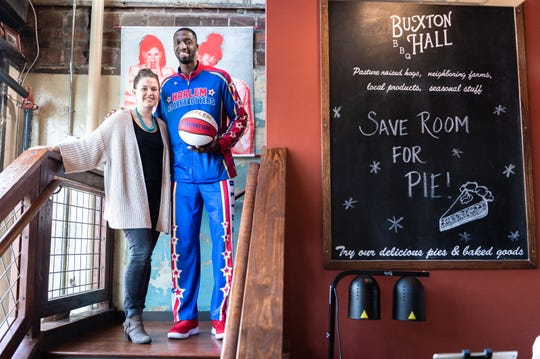 "Mackensy Lunsford, food writer at the Asheville Citizen Times, at Asheville's Buxton Hall BBQ with Chandler ""Bulldog"" Mack, a player on the Harlem Globetrotters exhibition basketball team and self-proclaimed foodie, Jan. 8, 2019. The team is playing at Asheville's U.S Cellular Center on Sunday, Jan. 13."