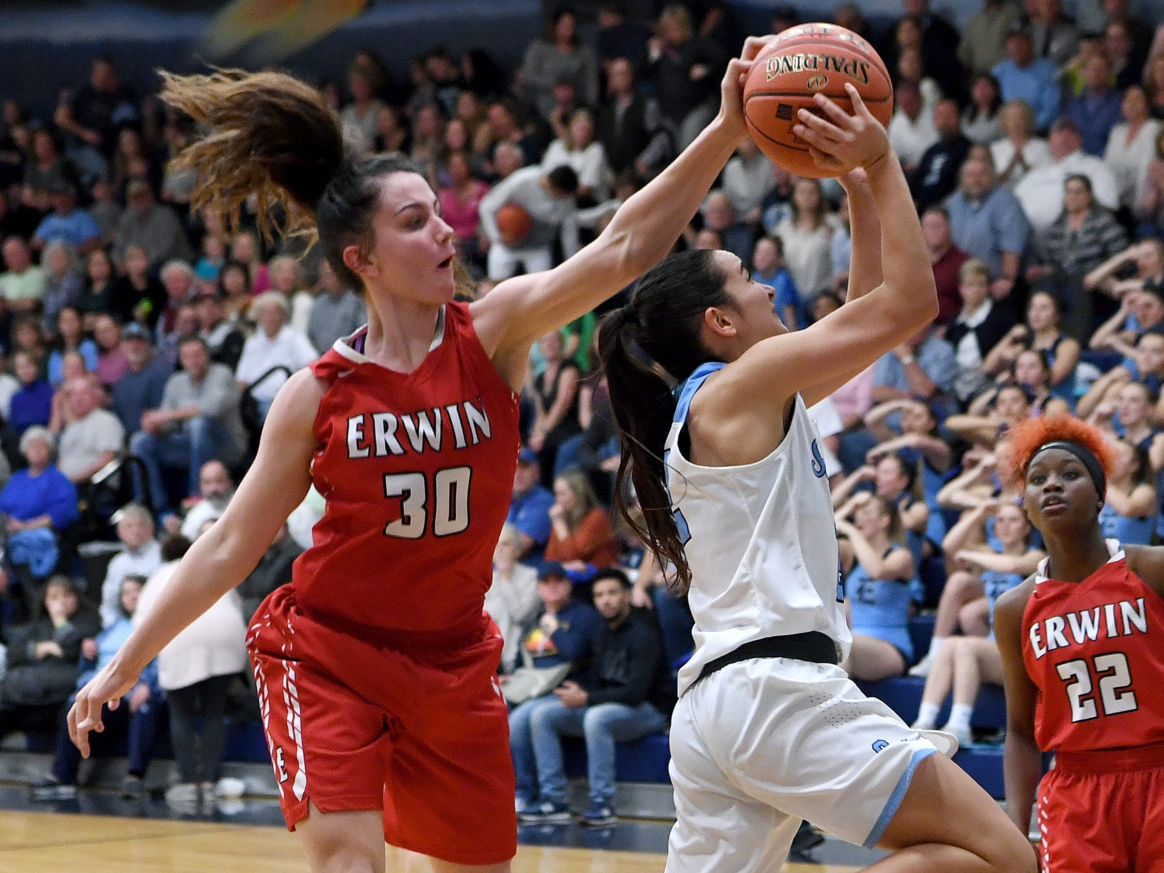 Erwin's Kaitlyn Messer gets a hand on the ball as Enka's Monica Garcia de Sivatte goes up for a shot during their game at Enka High School on Jan. 8, 2019. The Lady Warriors defeated the Sugar Jets 61-45.