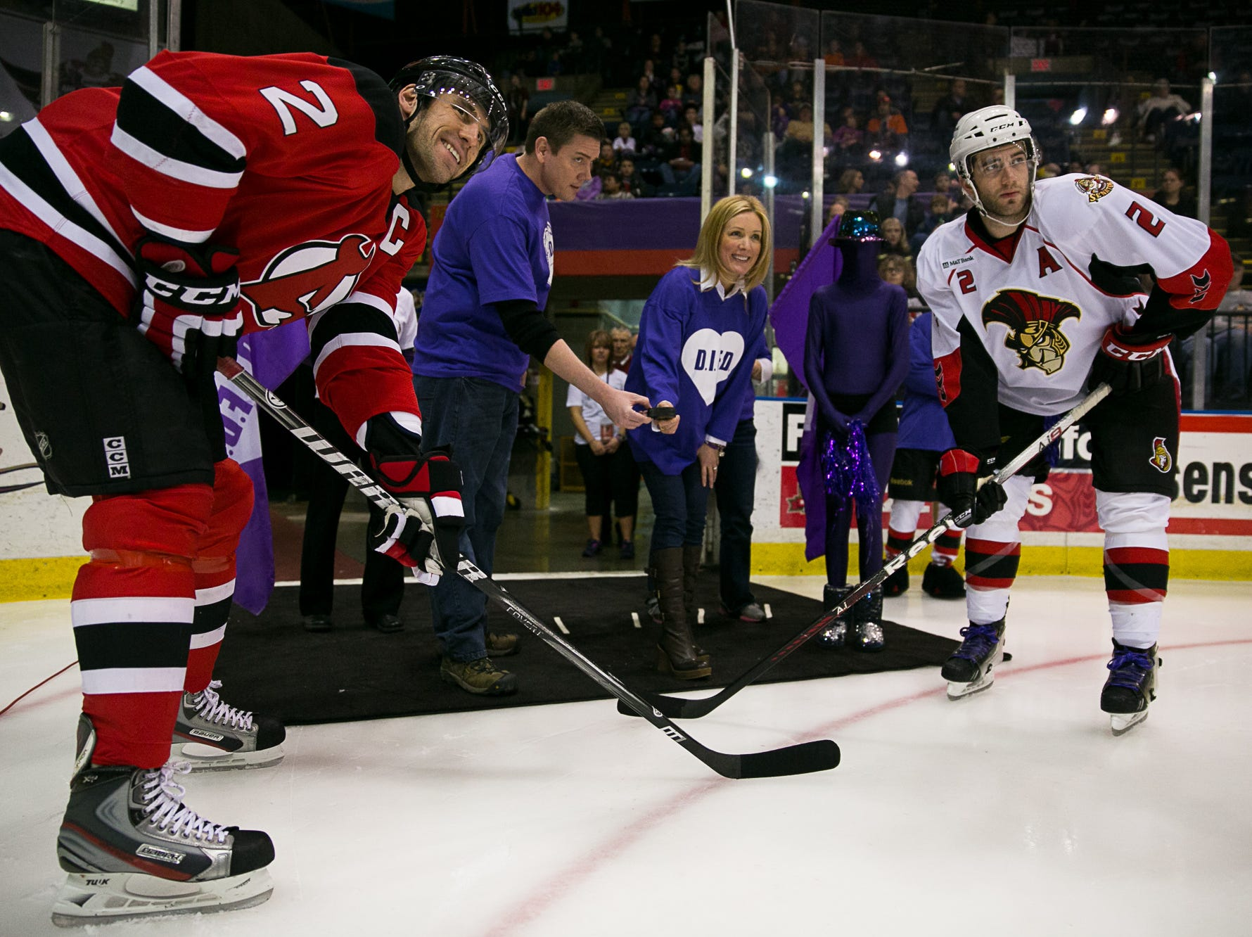 2013: Stephanie Richardson, center, the wife of Binghamton Senators coach Luke Richardson, helps drop the puck for the ceremonial faceoff Sunday night between Binghamton's Eric Gryba, right, and Albany's Jay Leach in February 2013.
