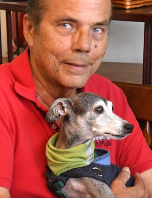 Bill Jacobson, seen here with his 17-year-old Italian greyhound, Miko, is the owner of the Puppies Plus pet store in Melbourne. He told county commissioners that the new county pet store ordinance would put him out of business.