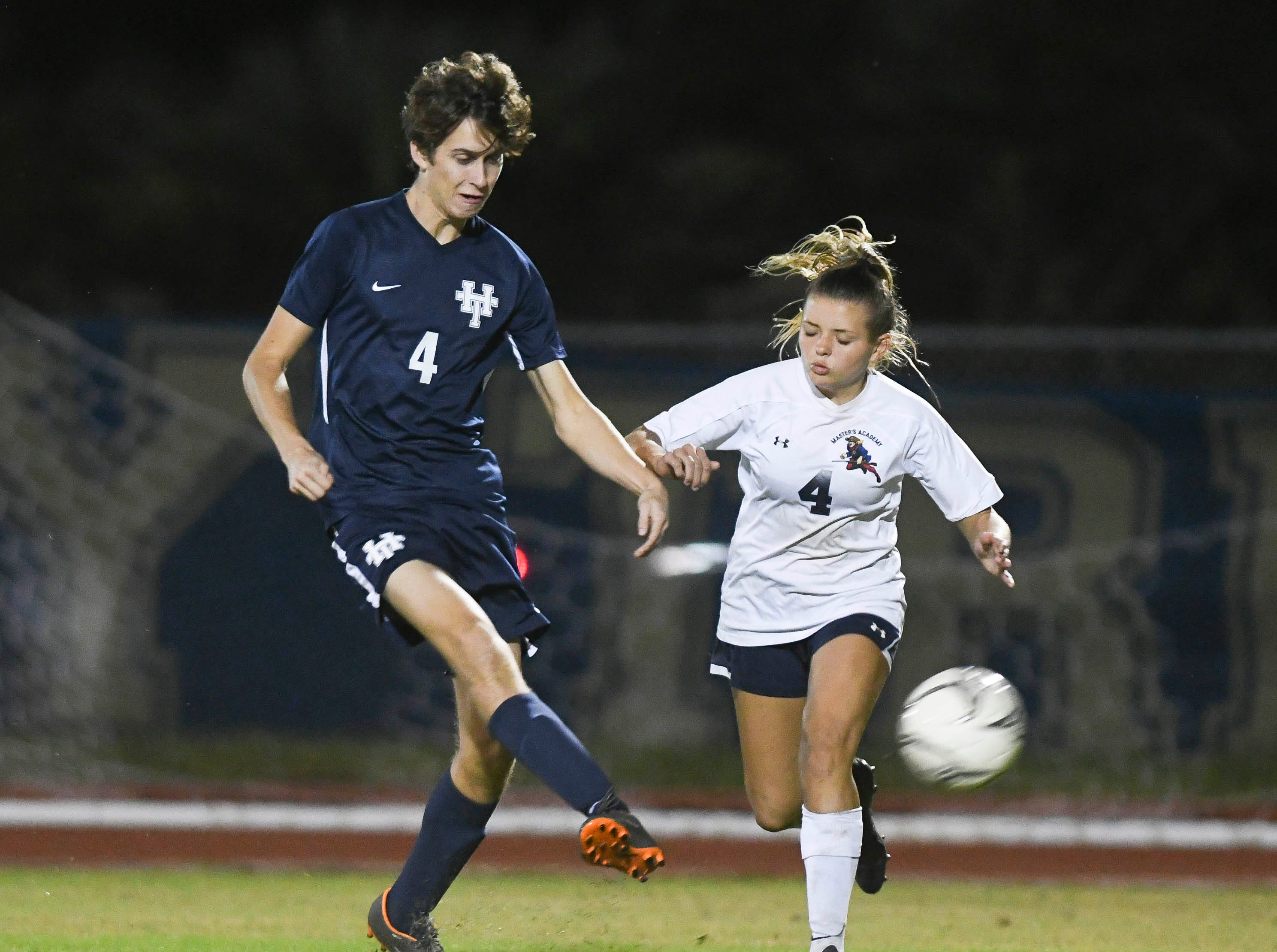 Holy Trinity's Charlie Woods is challenged by Sidney Rohm of Master's Academy during Tuesday's game.