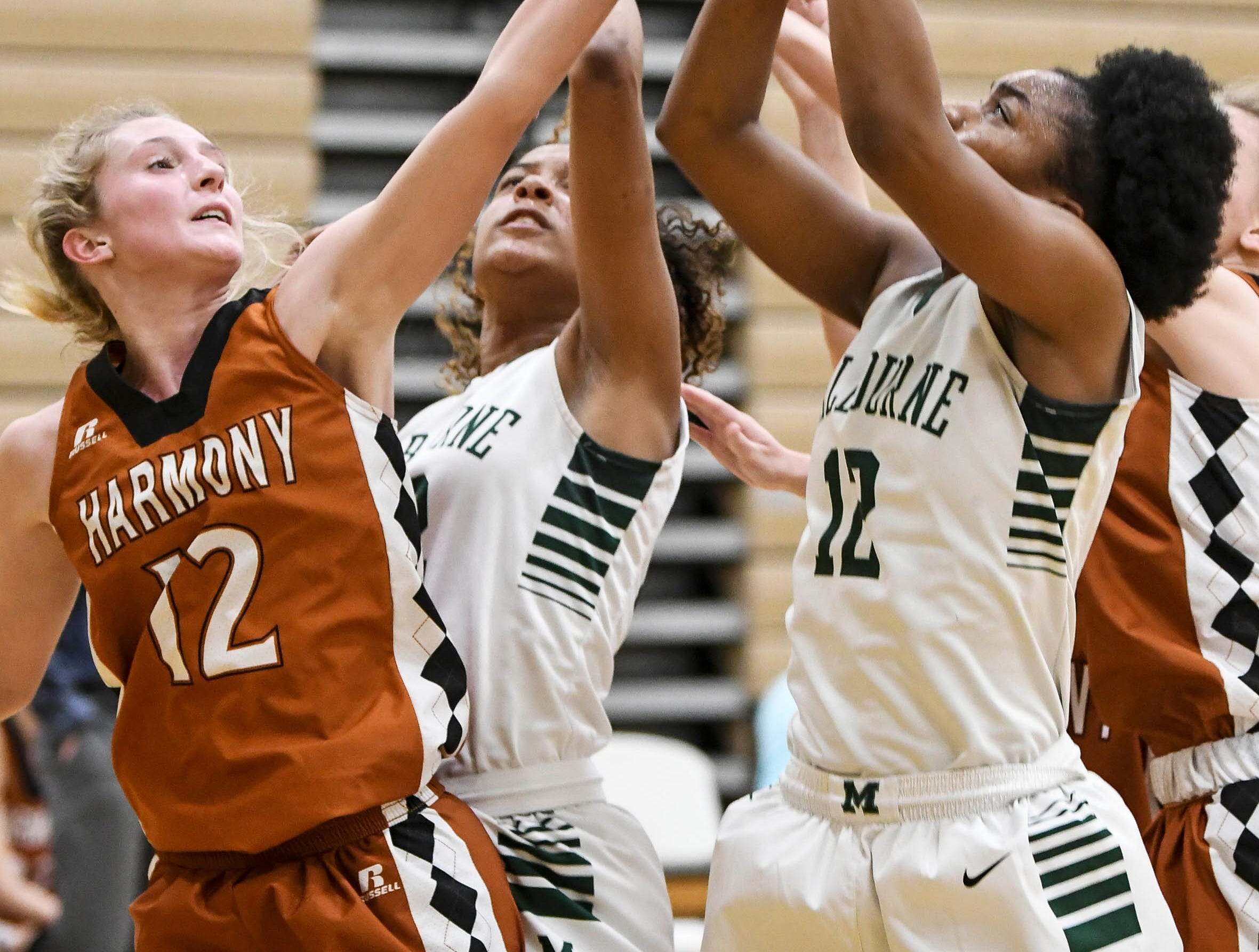 Allison Richardson of Harmony battles Mikyla Tolivert of Melbourne for a rebound Tuesday during their game at Melbourne High.