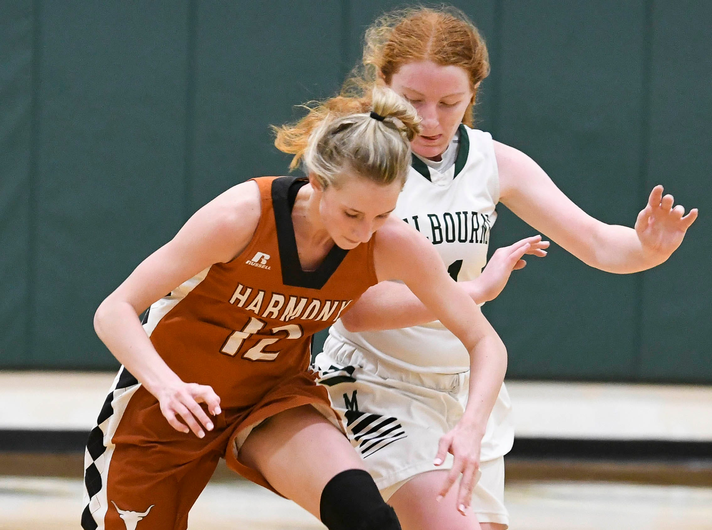 Allison Richardson of Harmony and Maggie Scott of Melbourne chase a loose ball during Tuesday's game.