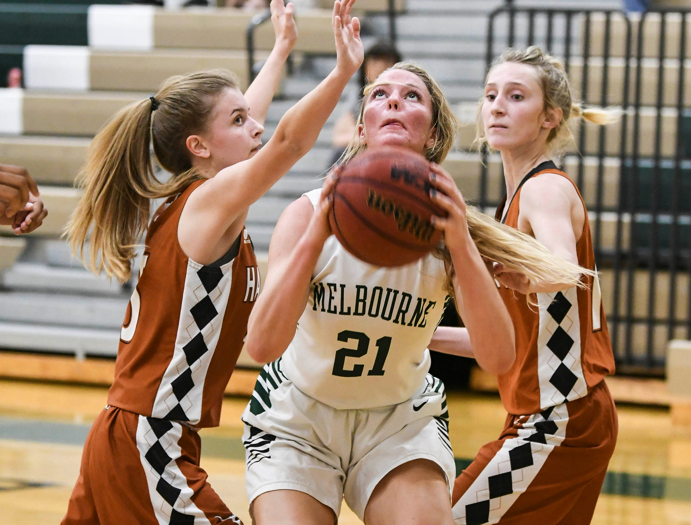 Ava Rowell of Melbourne shoots between Ty Green (3) and Allison Richardson of Harmony during Tuesday's game.