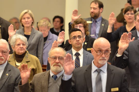 New and returning lawmakers including Nader Hashim, D-Dummerston, center, take the oath of office in the House of Representatives at the Statehouse in Montpelier on Jan. 9, 2019.