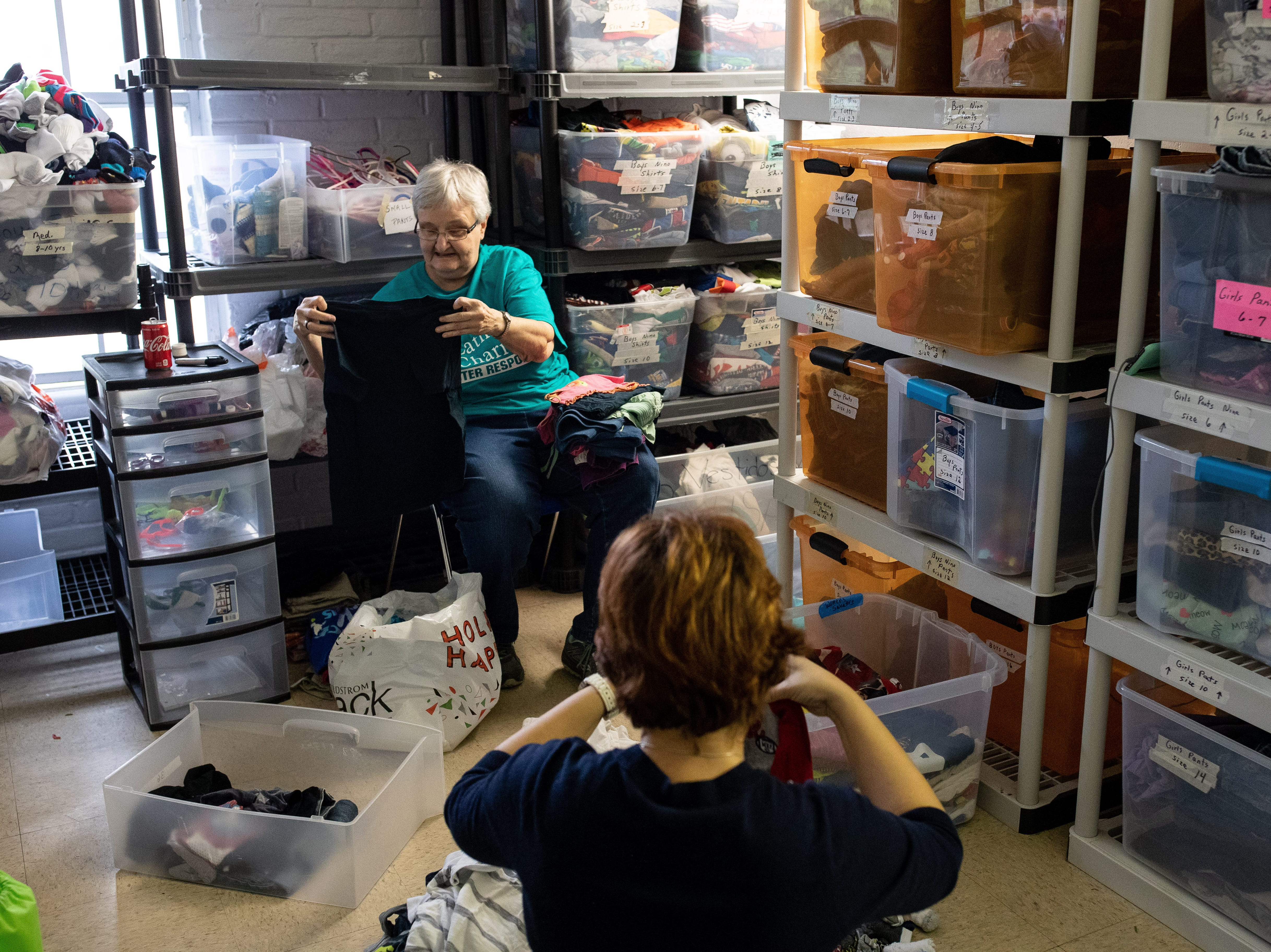 Volunteers at Catholic Charities of the Rio Grande Valley in McAllen, Tx fold donated clothing for migrants on Wednesday, Jan. 9, 2019.