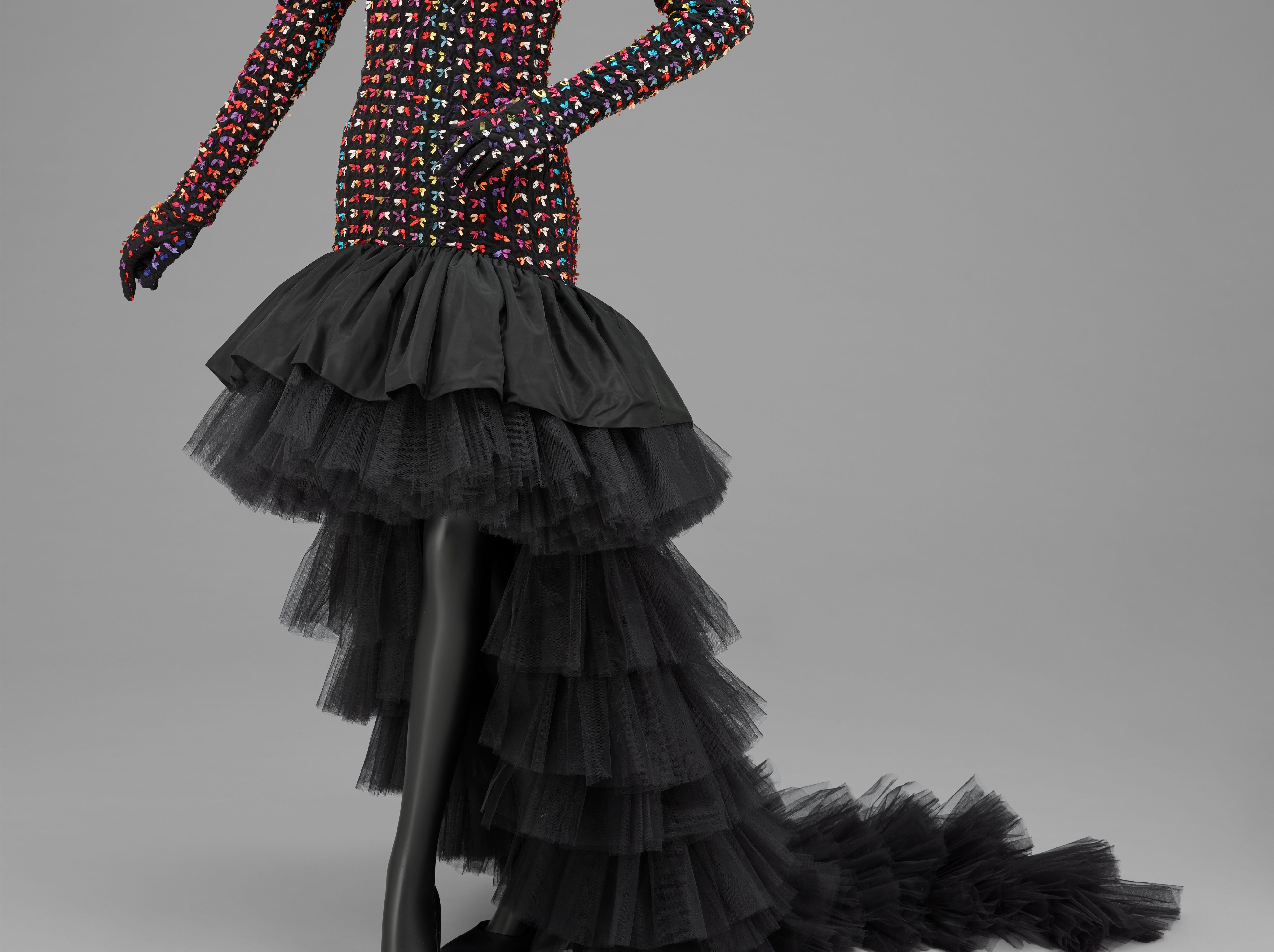 Designed by Patrick Kelly, 'Woman's Evening Dress and Two Pairs of Gloves' will be Fall/Winter 1988. Dress: Black nylon plain weave, machine embroidery over multicolored acetate plain weave ribbons, black triacetate taffeta and polyester net. Gloves: Black nylon plain weave, machine embroidery over multicolored acetate plain weave ribbons, black synthetic knit.