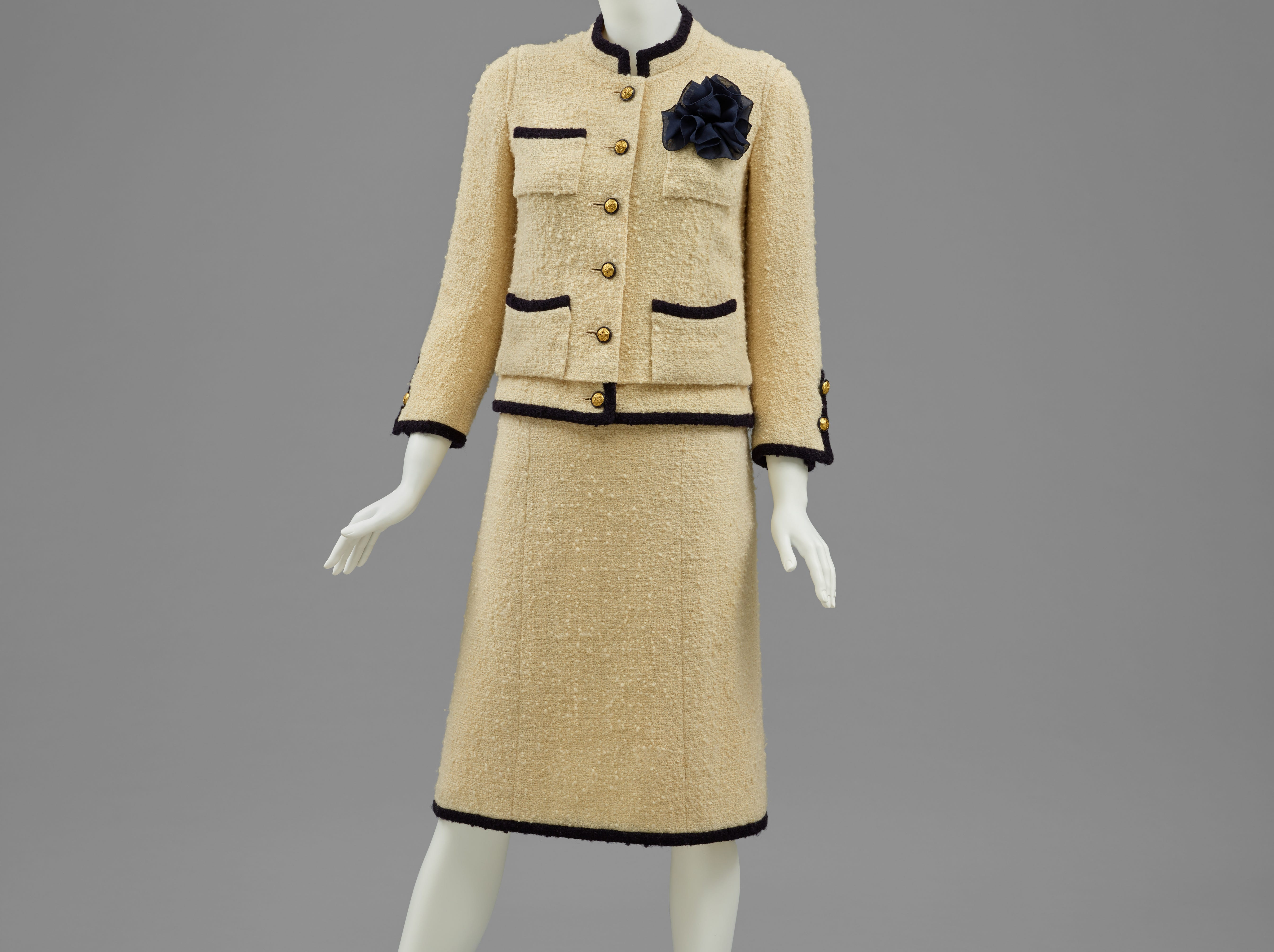 'Label Chanel, Paris  Woman's Suit: Jacket, Skirt, and Kerchief' was designed in Fall/Winter 1972-1973. The ensemble is an ivory and black wool and navy blue silk.