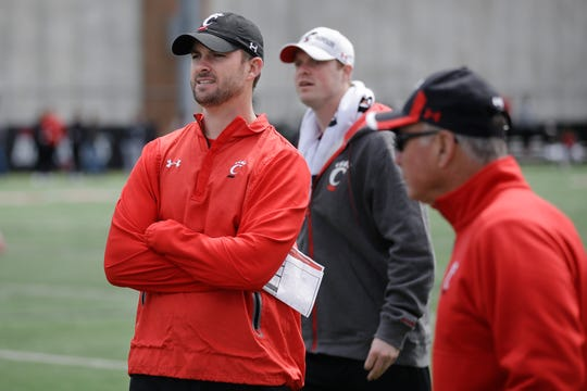 Cincinnati's offensive coordinator and quarterbacks coach Zac Taylor, left, works the sidelines during their spring NCAA college football game, Saturday, April 2, 2016, in Cincinnati. Taylor, the former offensive coordinator of the Miami Dolphins, was hired earlier this year to replace the vacant positions left by former UC offensive coordinator Eddie Gran and former UC quarterbacks coach Darin Hinshaw.