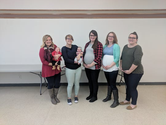 New moms and expecting moms pose for a photo at Girl Scouts of Greater Iowa. The organization just rolled out an infants-at-work policy to allow new parents to bring their children to the office full-time.