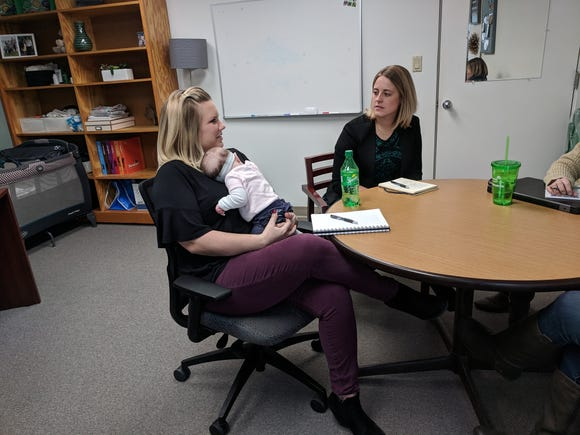 Chelsey DeRuyter, chief development officer at Girl Scouts of Greater Iowa, attends a recent meeting with her 14-week-old daughter, Finley, on her lap.