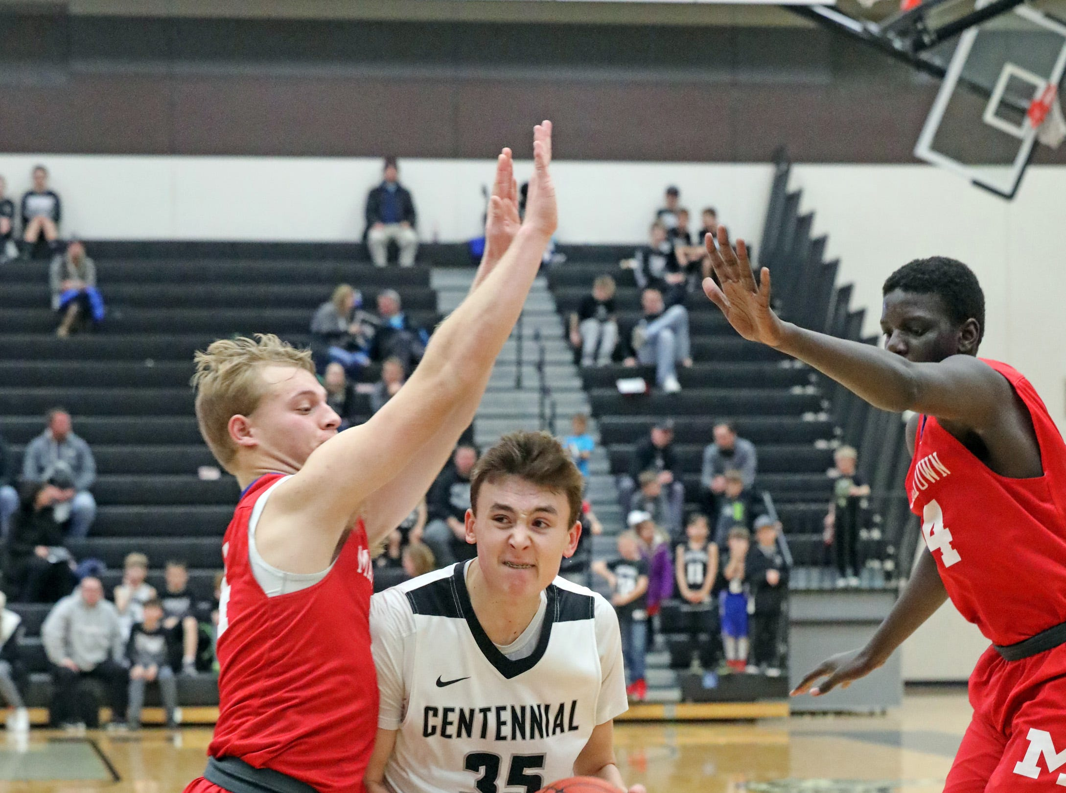 Ankeny Centennial junior Cody McCullough (35) splits through the defense as the Marshalltown Bobcats compete against the Ankeny Centennial Jaguars in high school boys basketball on Tuesday, Jan. 8, 2019 at Ankeny Centennial High. Marshalltown rallied to win 63 to 60 in double overtime.