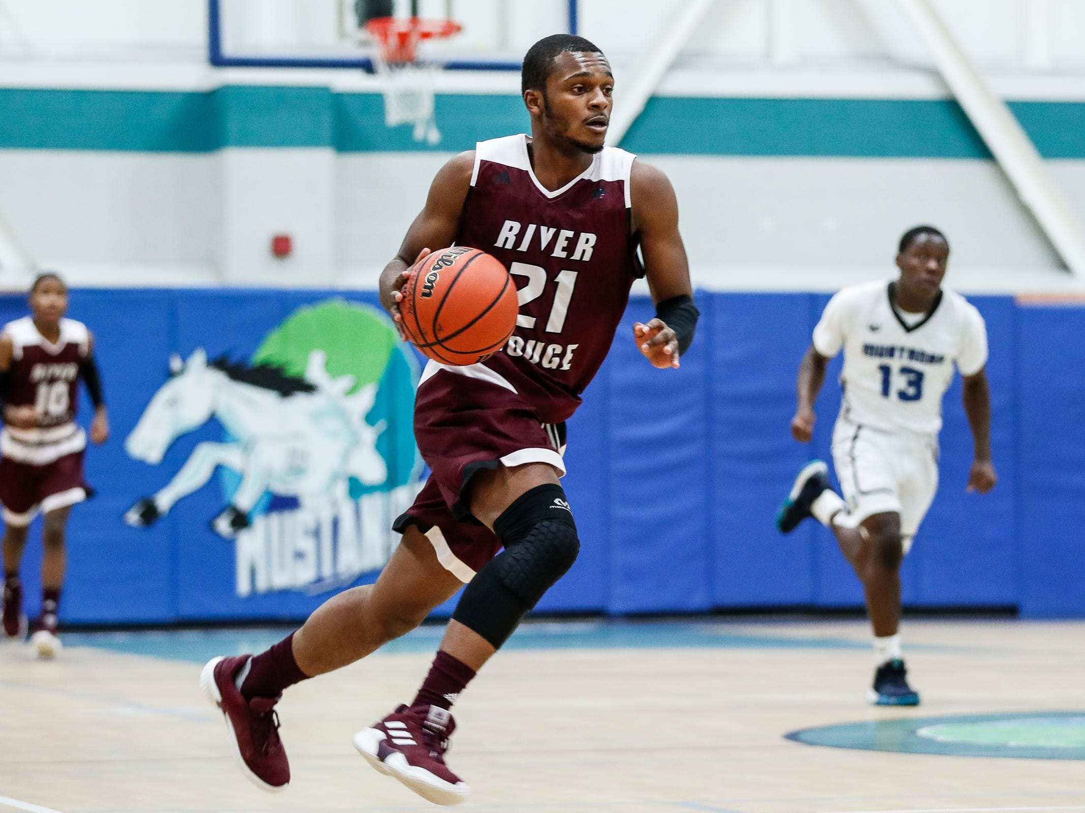 River Rouge's Nigel Colvin (21) dribbles against Henry Ford Academy: School for Creative Studies during first half at the A. Alfred Taubman Center For Design Education in Detroit, Tuesday, Jan. 8, 2019.