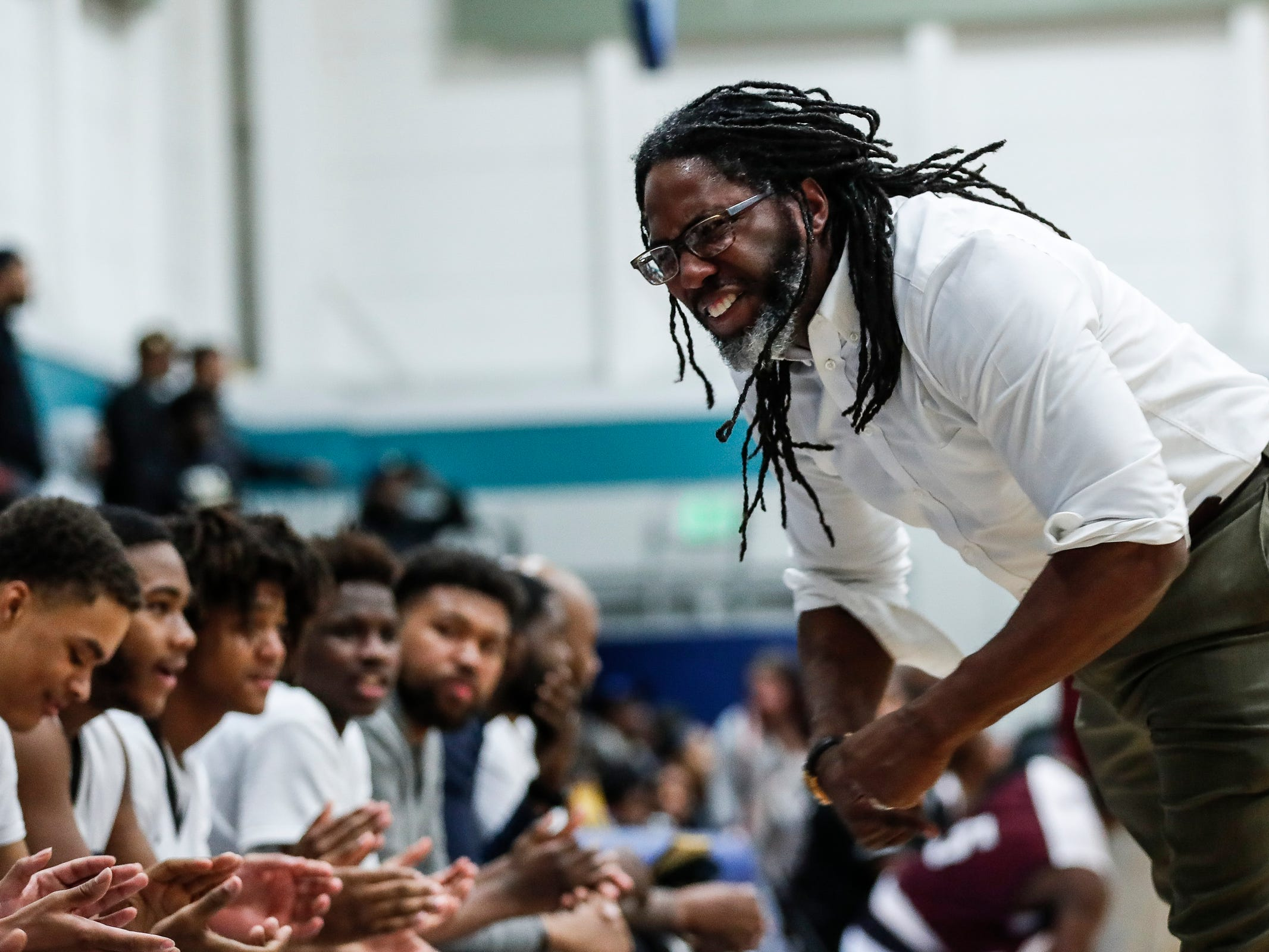 Henry Ford Academy: School for Creative Studies head basketball coach Taurean Wilson celebrates a play with players during first half at the A. Alfred Taubman Center For Design Education in Detroit, Tuesday, Jan. 8, 2019.