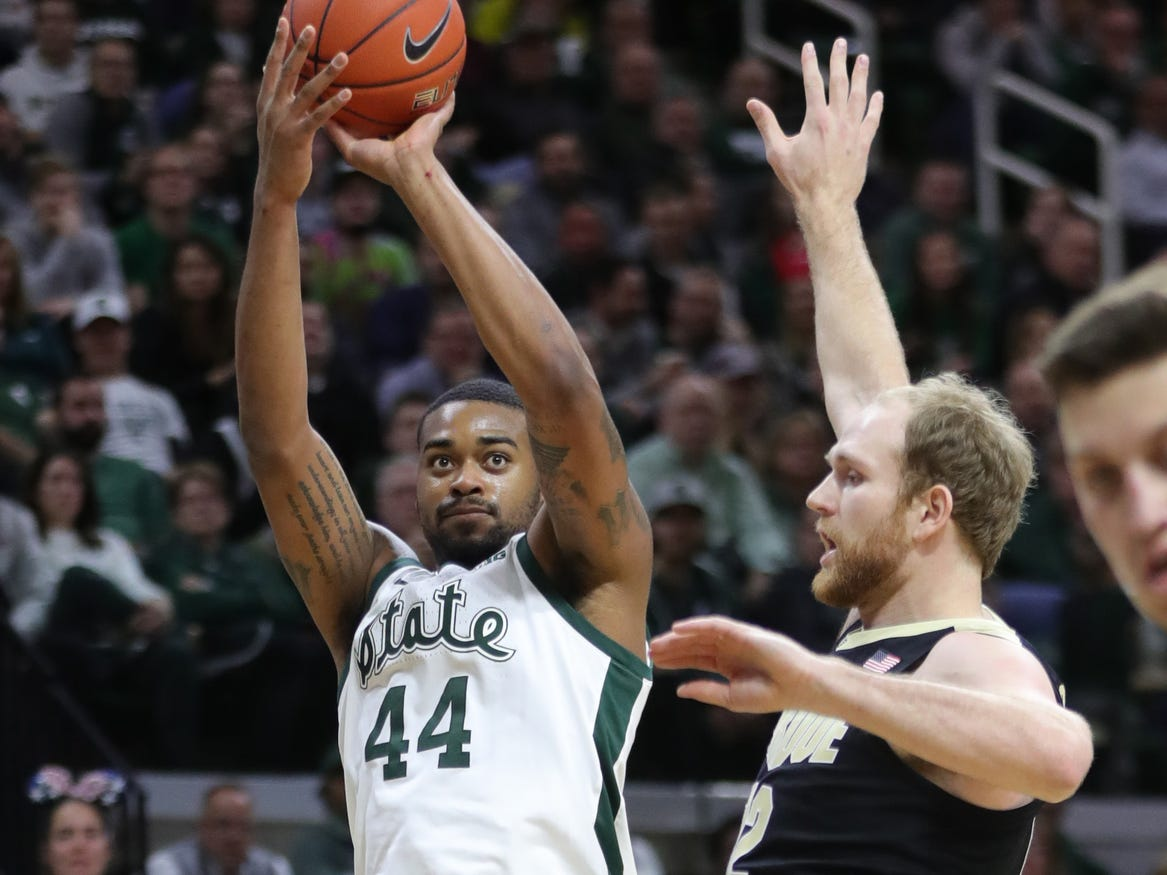 Michigan State forward Nick Ward scores against Purdue forward Evan Boudreaux during first half action Tuesday, Jan. 8, 2019 at the Breslin Center in East Lansing, Mich.
