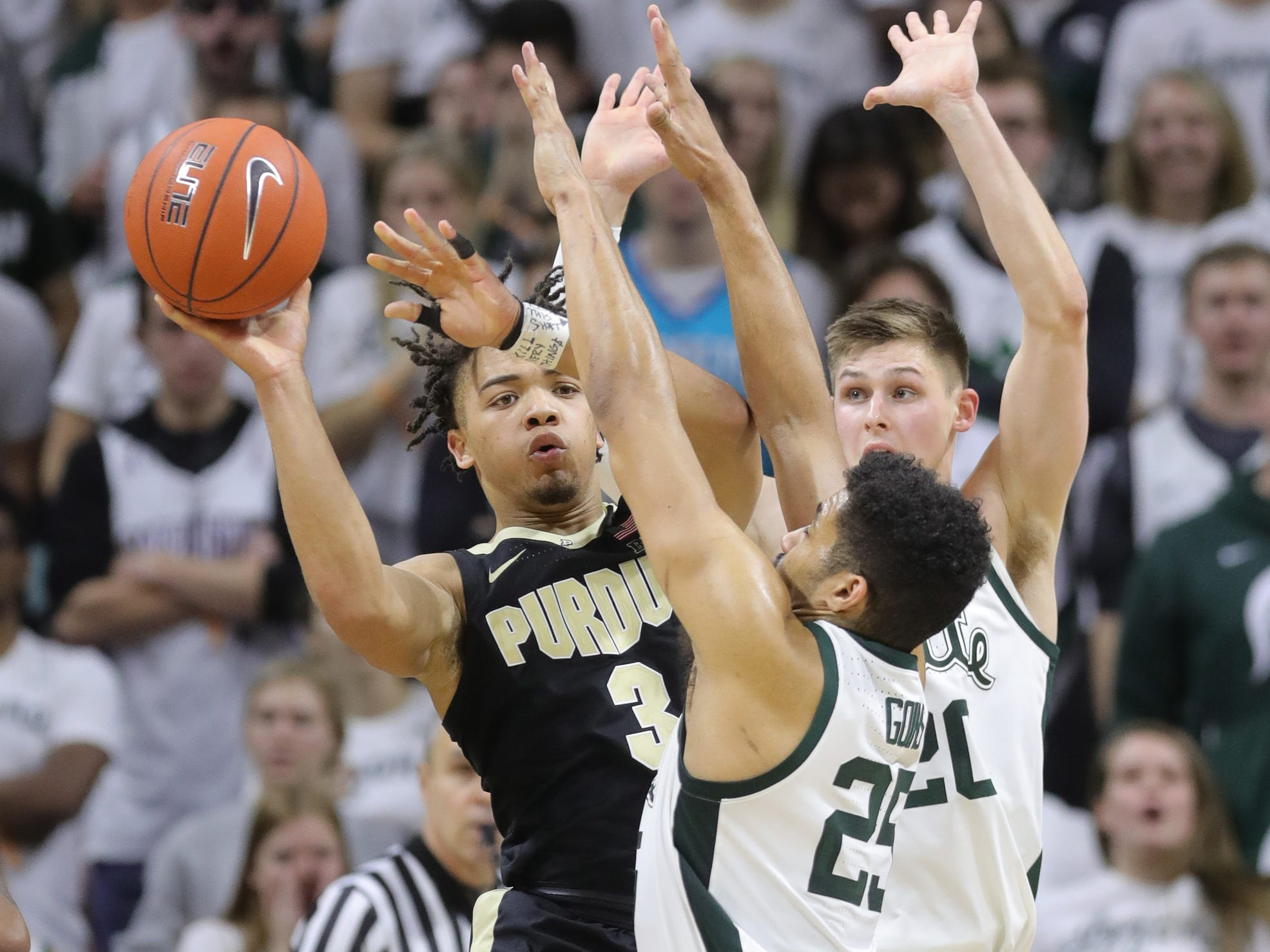 Michigan State's Matt McQuaid (20) and Kenny Goins (25) defend Purdue's Carsen Edwards, Jan. 8, 2019 at the Breslin Center in East Lansing.